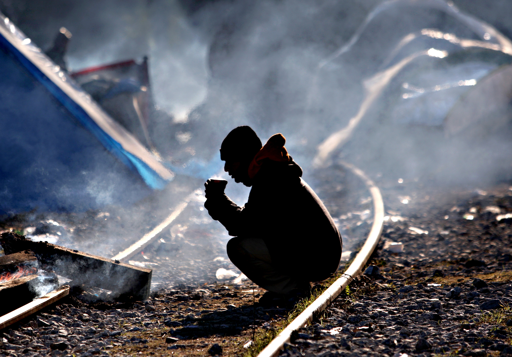 A man sits on rail tracks as migrants and refugees wait to cross the Greek-Macedonian border near Idomeni on December 8, 2015.  Since last week, Macedonia has restricted passage to northern Europe to only Syrians, Iraqis and Afghans who are considered war refugees. All other nationalities are deemed economic migrants and told to turn back, leaving over 1,500 people stuck on the border, mostly Indian, Moroccan, Bangladeshi and Pakistani.
