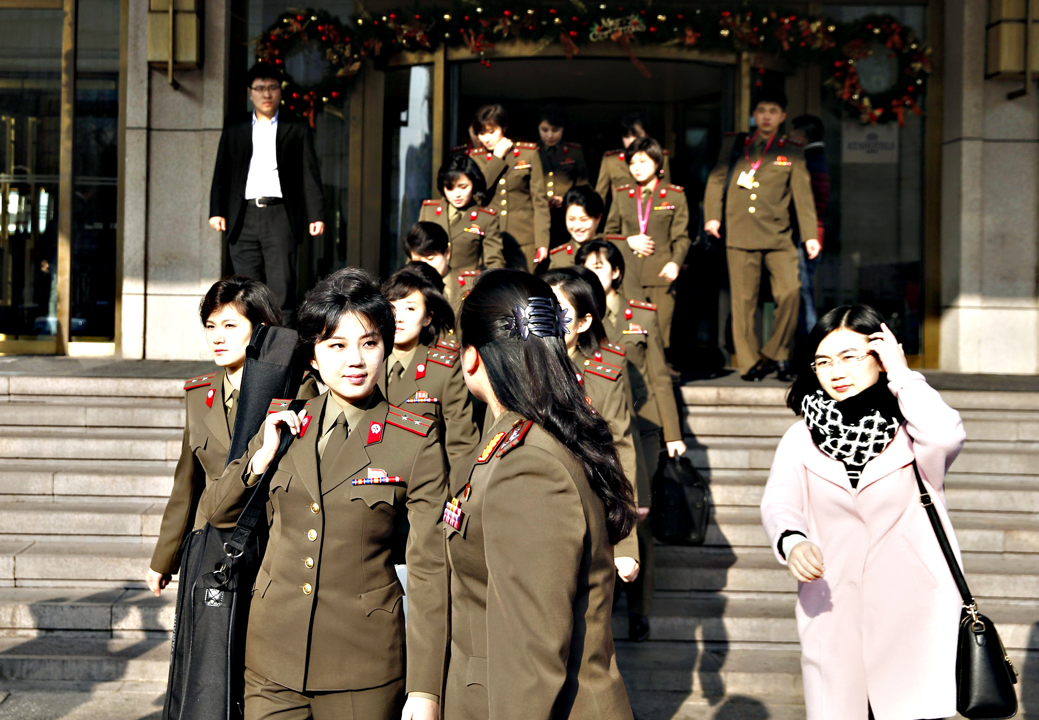 Members from North Korea's Moranbong band walk out of their hotel in Beijing on Friday. North Korea's premier pop group, the all-girl Moranbong band formed by leader Kim Jong-Un, is electrifying audiences in China in shows aimed at harmonising out-of-tune ties between the traditional allies