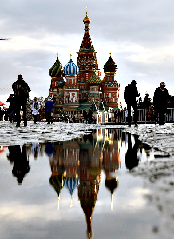 People walk across Red Square, with St. Basil's Cathedral seen in the background, in central Moscow on December 22, 2015. The temperatures in the Russian capital reached today 6 C (42 F)
