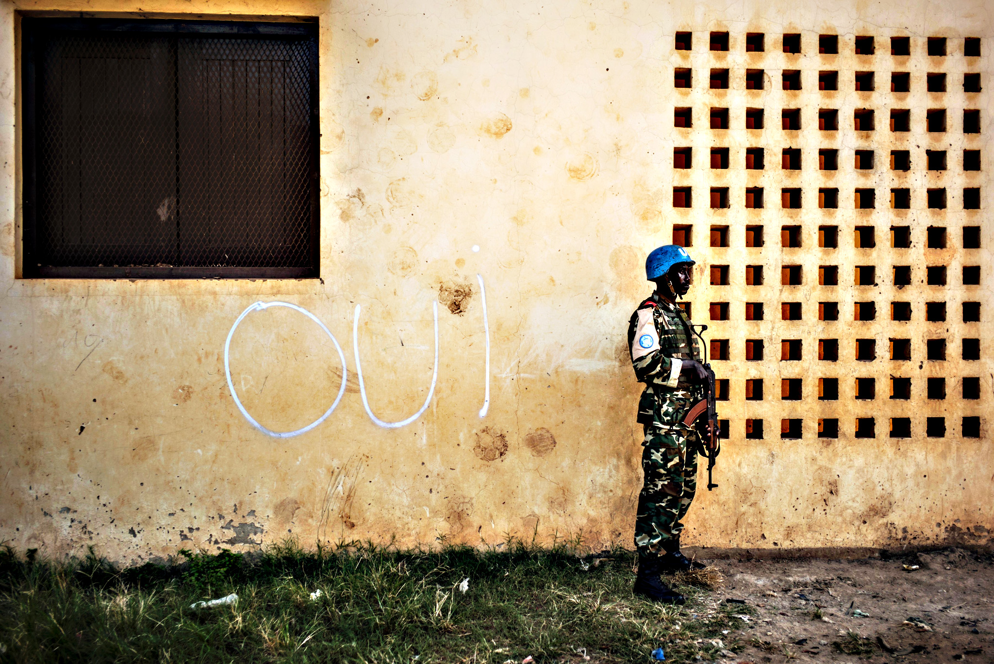 """Oui"" (Yes) is seen written on the walls of a polling station, where a soldier of the UN peacekeeping force MINUSCA contingent is on guard on December 14, 2015. Another two people died overnight in the Central African Republic capital Bangui, the Red Cross said on December 14, bringing the death toll from unrest sparked by a constitutional referendum to five. Clashes involving rocket launchers and machine guns disrupted the polling on December 13 in the Muslim-majority PK-5 district of Bangui. The vote is seen as a test run for presidential and parliamentary elections due to take place December 27 to end more than two years of conflict between the Muslim and Christian militias."