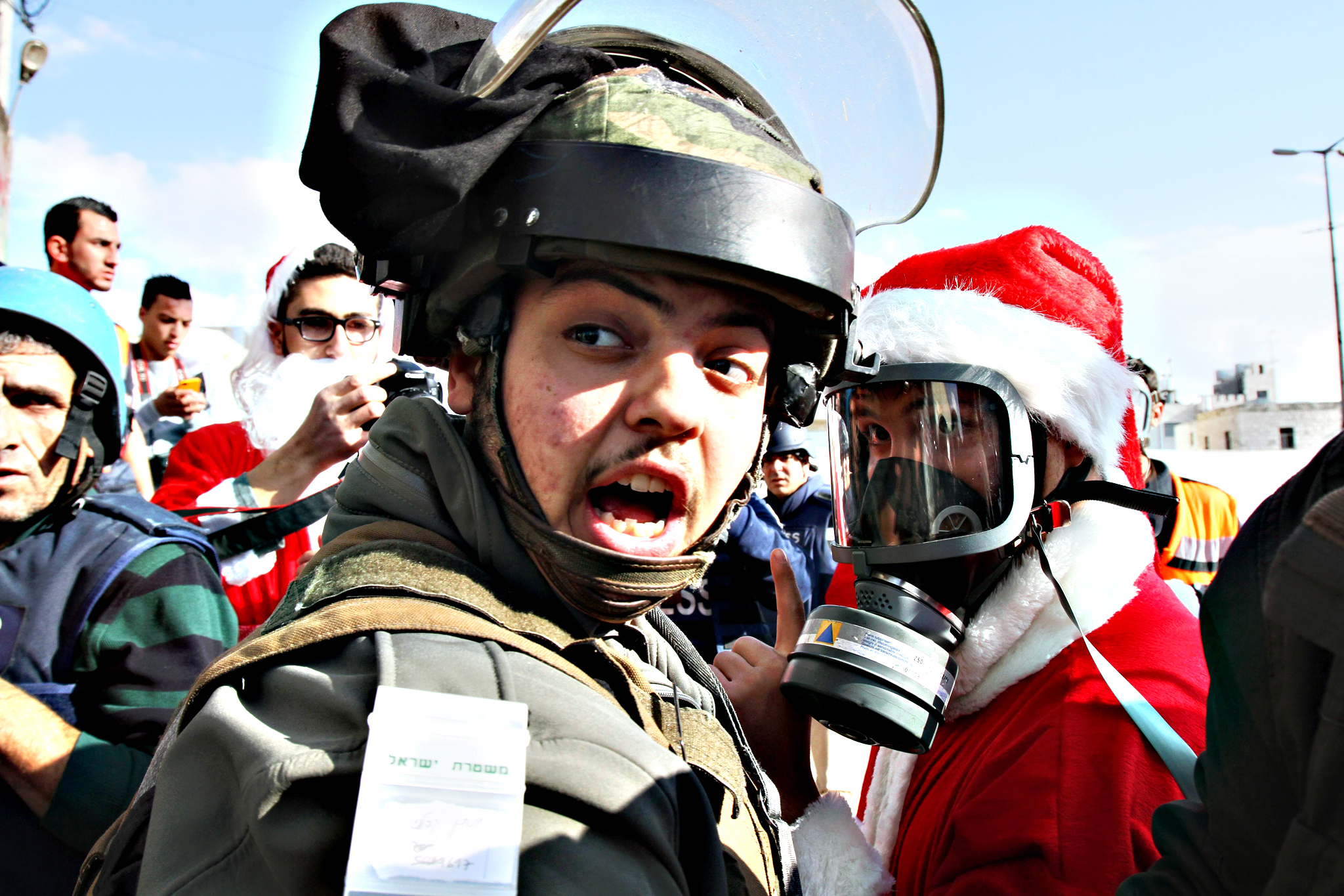 A Palestinian dressed up as Santa Claus talks to an Israeli soldier during a demonstration in front of a gate along the Israeli controversial separation wall in the West Bank city of Bethlehem, on December 18, 2015.