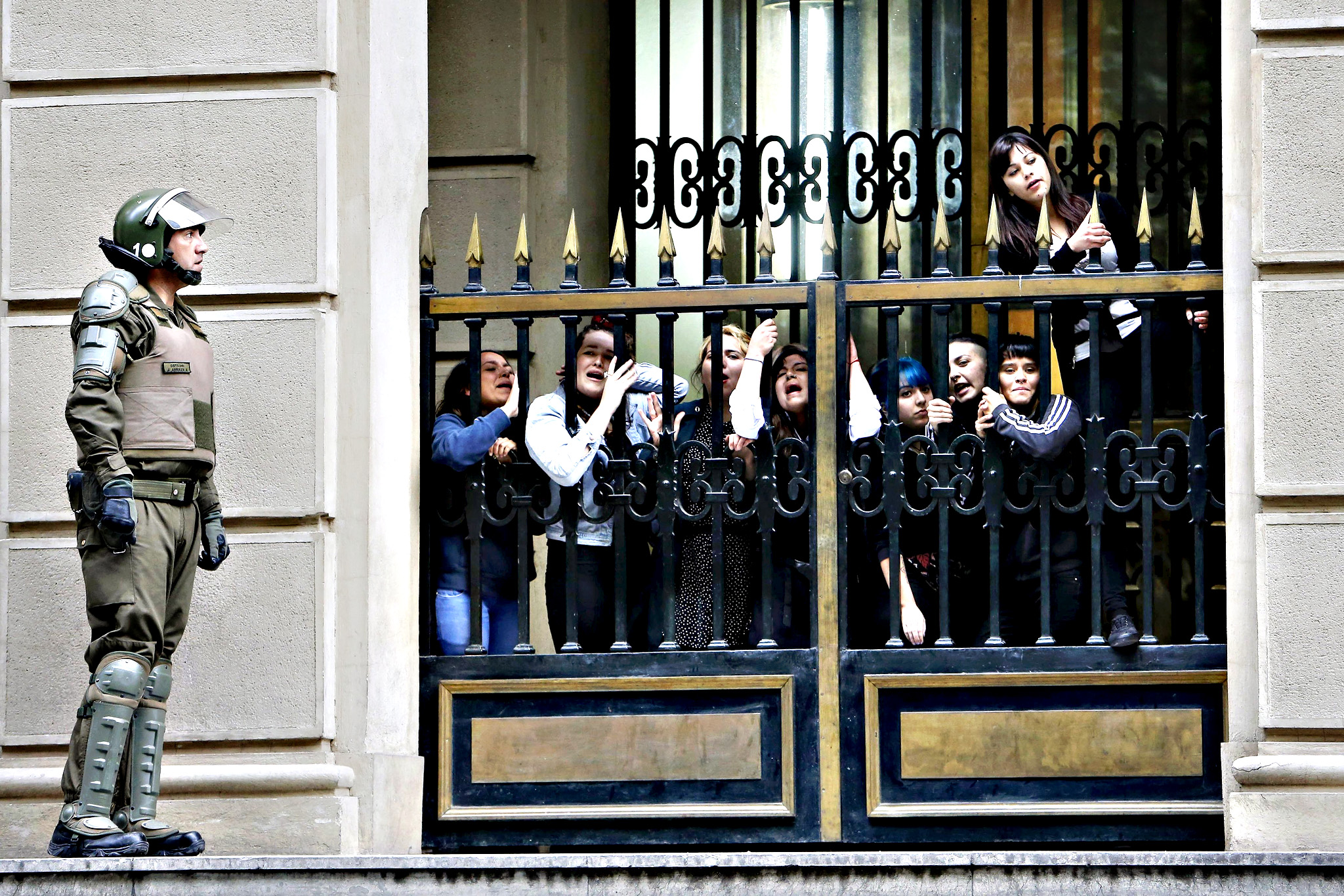Students cling to a fence as they occupy the Finance Ministry in downtown Santiago, December 21, 2015. Student protesters occupied the building as part of a protest demanding changes in the education system