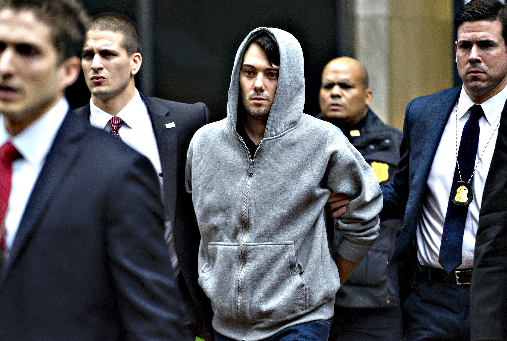 Martin Shkreli, the former hedge fund manager under fire for buying a pharmaceutical company and ratcheting up the price of a life-saving drug, is escorted by law enforcement agents in New York Thursday, Dec. 17, 2015, after being taken into custody following a securities probe. A seven-count indictment unsealed in Brooklyn federal court Thursday charged Shkreli with conspiracy to commit securities fraud, conspiracy to commit wire fraud and securities fraud.