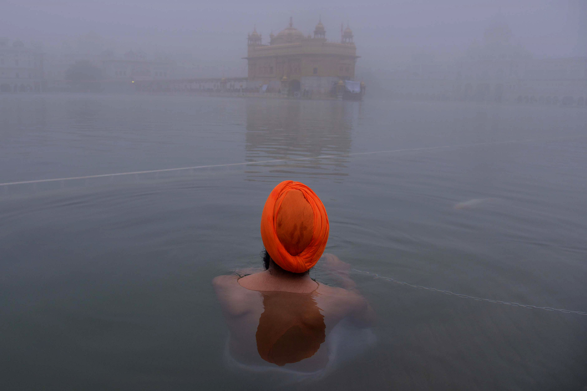 An Indian Sikh devotee takes a dip in the holy sarover (water tank) during dense fog at the Golden Temple in Amritsar