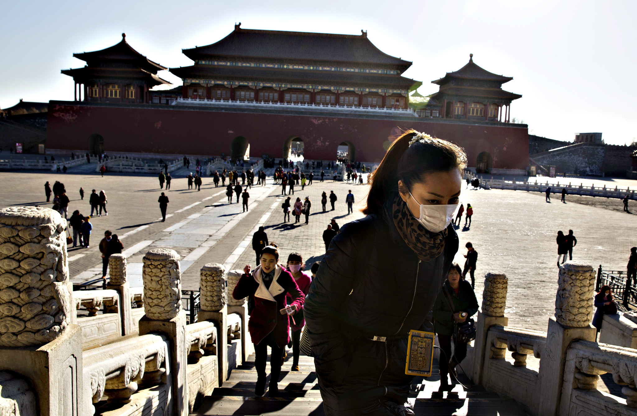 A woman wears a mask as she visits the Forbidden City during a sunny day in Beijing Friday, Dec. 18, 2015. Residents in the Chinese capital are preparing for its second smog red alert as a wave of smog is forecasted to settle over the city from Saturday to Tuesday.
