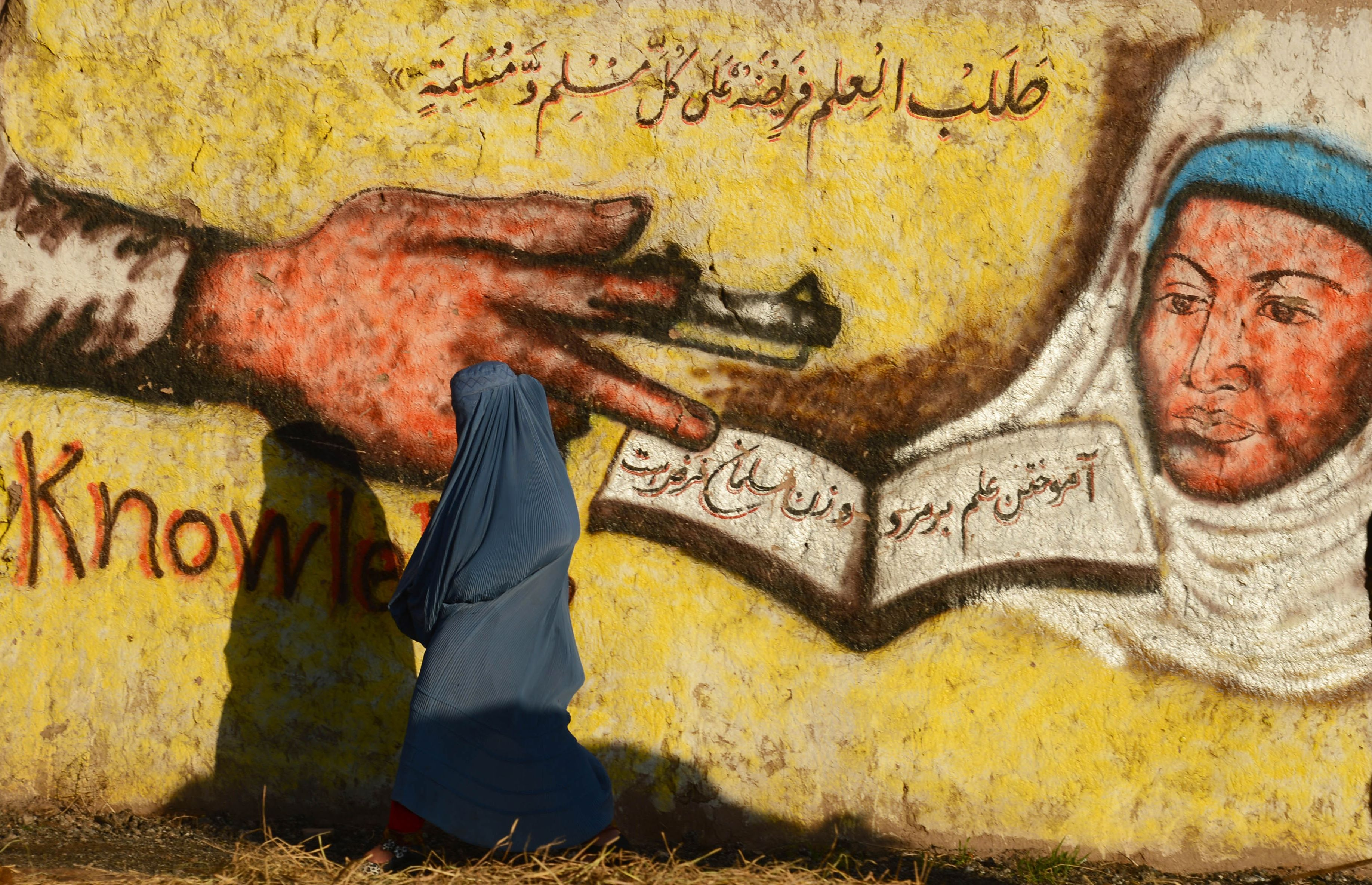 "In this photograph taken on January 27, ...In this photograph taken on January 27, 2016 an Afghan woman walks past a mural that also reads ""seeking knowledge is obligatory on every Muslim man and woman"" in Herat.  AFP PHOTO / Aref KarimiAref Karimi/AFP/Getty Images"