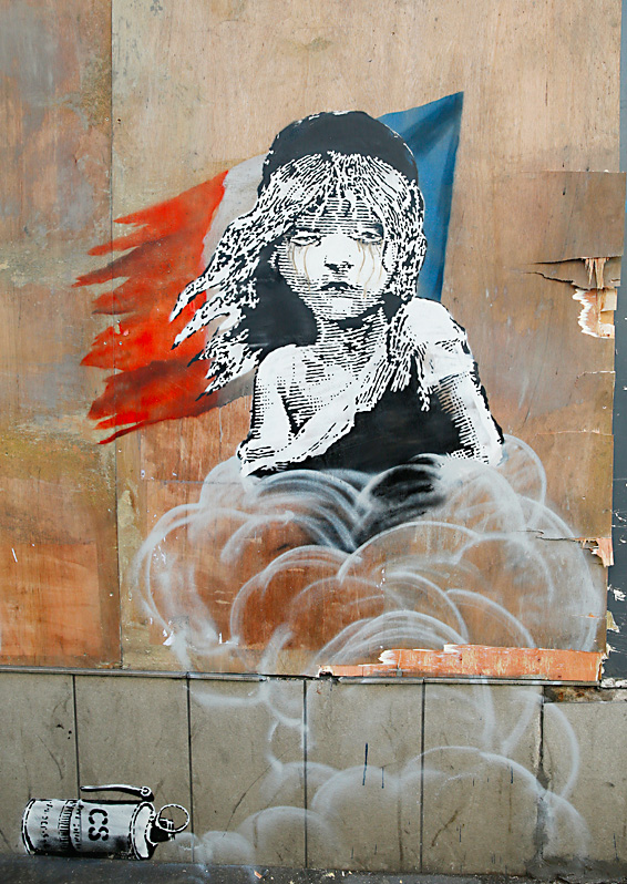 A new artwork by British artist Banksy opposite the French Embassy, in London, Monday, Jan. 25, 2016. The artwork depicts the young girl from the musical Les Miserables with tears streaming from her eyes as a can of CS gas lies beneath her. The work is criticising the use of teargas in the refugee camp in Calais. (AP Photo/Alastair Grant)