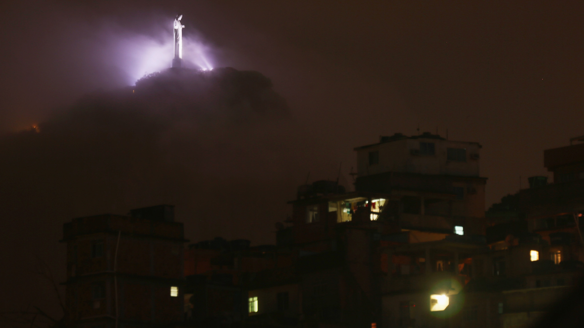 Fog Hovers Beneath Christ the Redeemer Statue...RIO DE JANEIRO, BRAZIL - JANUARY 04:  Fog hovers beneath Christ the Redeemer statue with the Cantagalo 'favela' in the foreground on January 4, 2016 in Rio de Janeiro, Brazil. The Rio 2016 Olympic Games commence in August.  (Photo by Mario Tama/Getty Images)