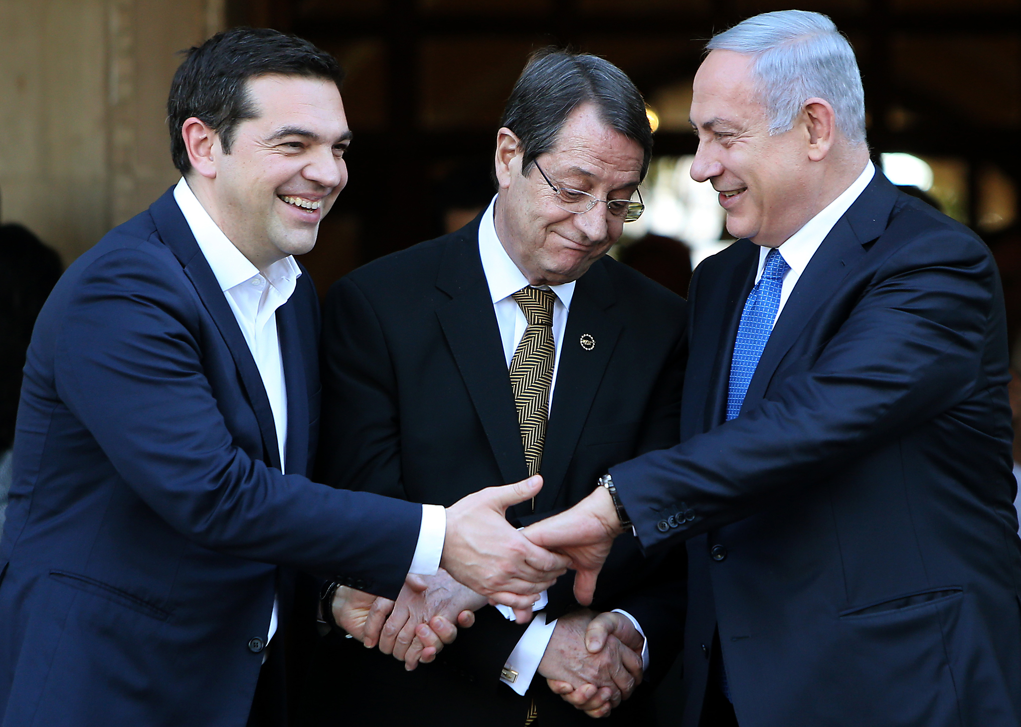 Nicos Anastasides, Alexis Tsipras, Benjamin Netanyahu...Cypriot president Nicos Anastasides, centre, Greek Prime Minister Alexis Tsipras, left, and  Israeli Prime Minister Benjamin Netanyahu shake hands after leaving their meeting from the presidential palace in capital Nicosia in the Mediterranean island of Cyprus, Thursday, Jan. 28, 2016. The leaders of Cyprus, Greece and Israel met in the Cypriot capital with the aim to strengthen cooperation and bolster stability in a region wracked by conflict. The talks are the first tripartite summit. Discussions will cover newly found offshore gas reserves and tourism, while the leaders will sign a cooperation agreement on water resources. (AP Photo/Petros Karadjias)