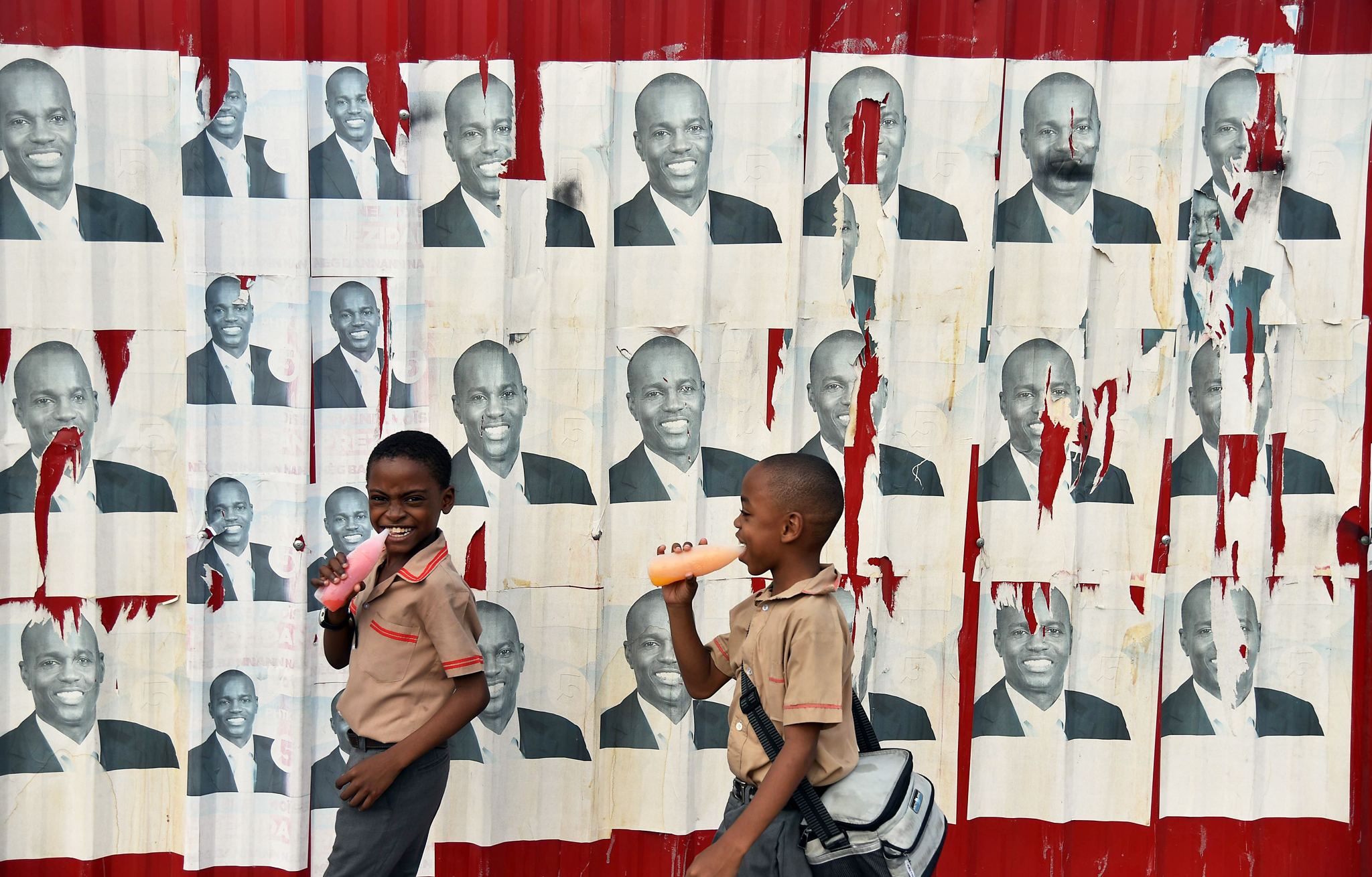 Children walk past election po...TOPSHOT - Children walk past election poster of presidential candidate Jovenel Moise of PHTK political party in Port-au-Prince on January 21, 2016.  The second round of presidential elections is scheduled for January 24 between ruling party candidate Jovenel Moise and Jude Celestin. Celestin has said he does not want to participate in the January 24 run-off against Moise, who has yet to submit his official resignation to the Provisional Electoral Council(CEP) / AFP / HECTOR RETAMALHECTOR RETAMAL/AFP/Getty Images