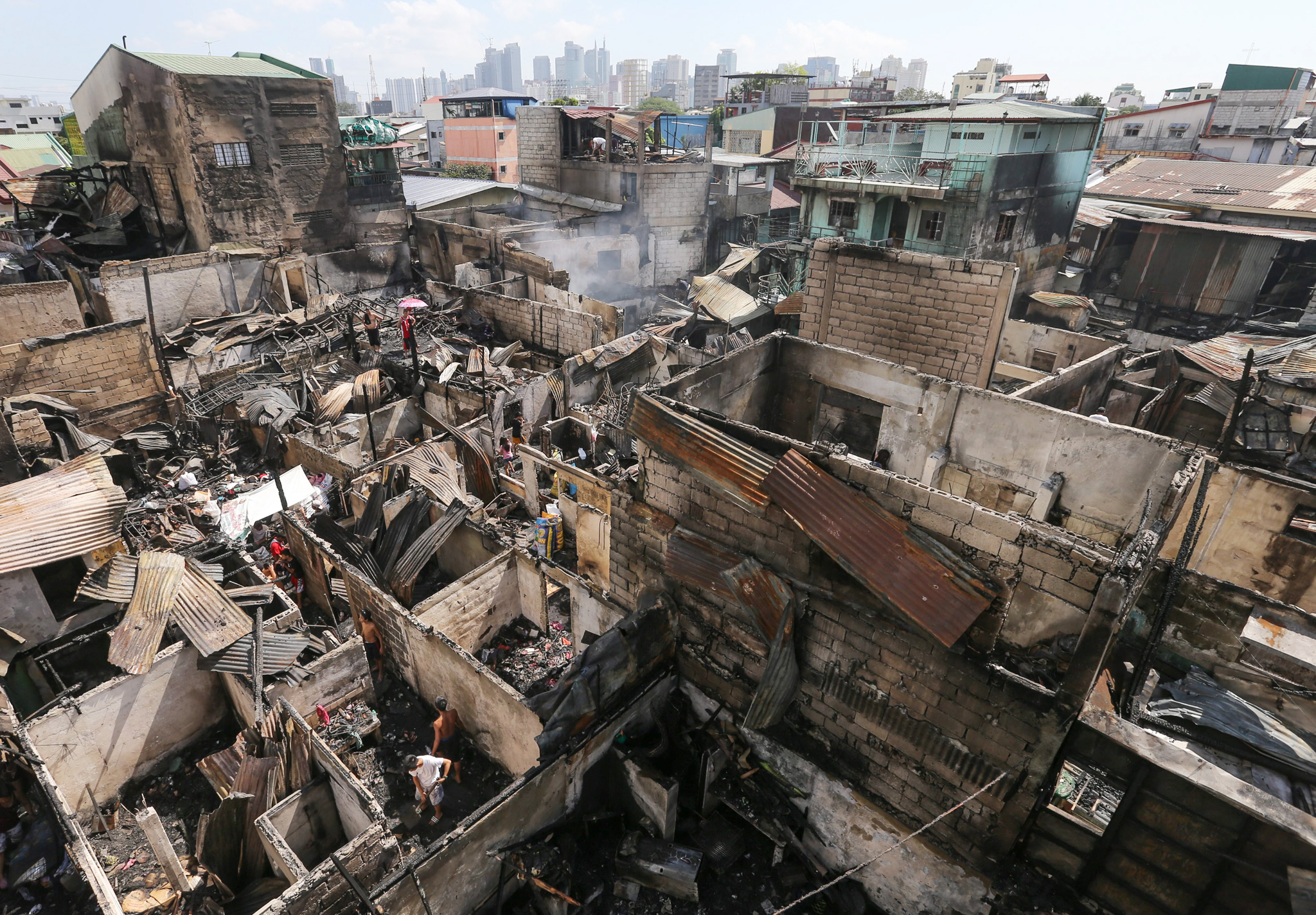 Fire in Manila leaves 80 families homeless...epa05115144 Filipinos search for salvageable materials following a fire in Manila, Philippines, 21 January 2016. The fire which hit a residential area in Manila left 80 families homeless according to local reports.  EPA/MARK R. CRISTINO
