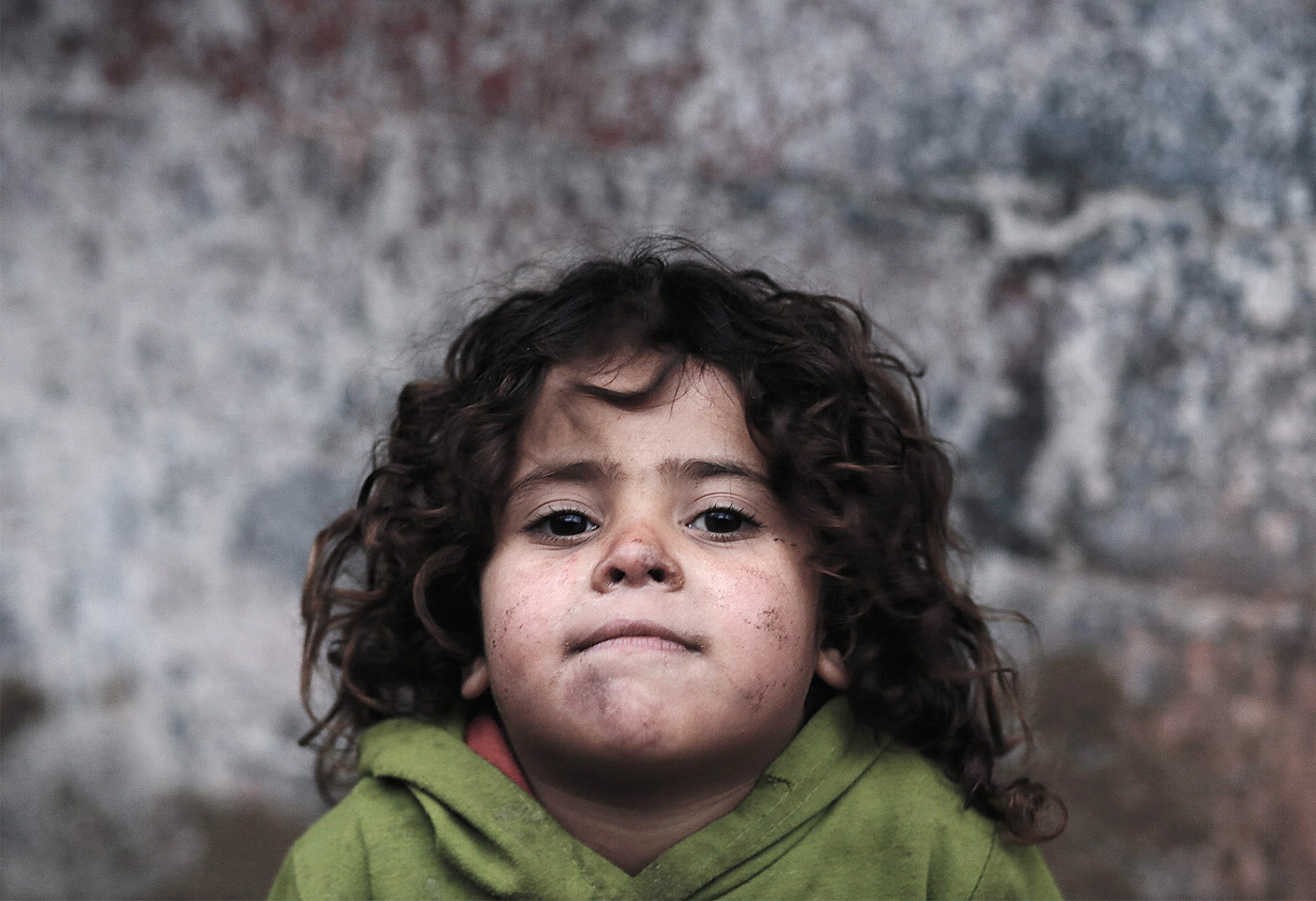 Palestinian refugee children during cold weather in Gaza City...epa05125781 A Palestinian refugee girl poses for a photograph outside her family's small house during cold weather on a rainy day in Gaza City, the Gaza Strip, 25 January 2016.