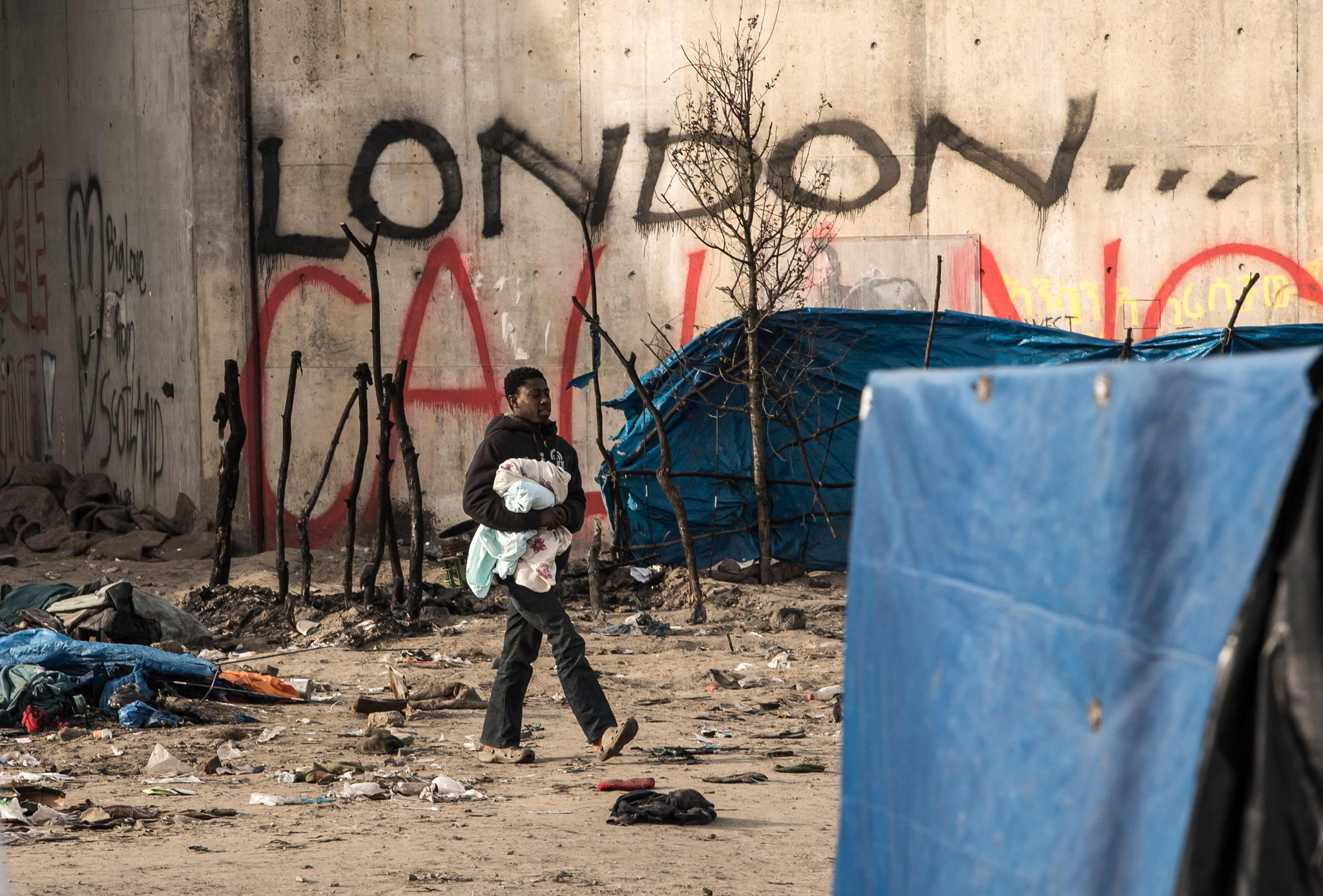 """A man walks in a makeshift camp known as...A man walks in a makeshift camp known as """"the jungle"""", on January 18, 2016 in Calais.  The residents of the camp in the northern French port of Calais are in a desperate race to save their makeshift homes from the bulldozers. Local authorities warned them earlier this week that they had just a few days to clear hundreds of shanties made from wooden planks and tarpaulin from the edge of the road that borders the camp.  / AFP / PHILIPPE HUGUENPHILIPPE HUGUEN/AFP/Getty Images"""