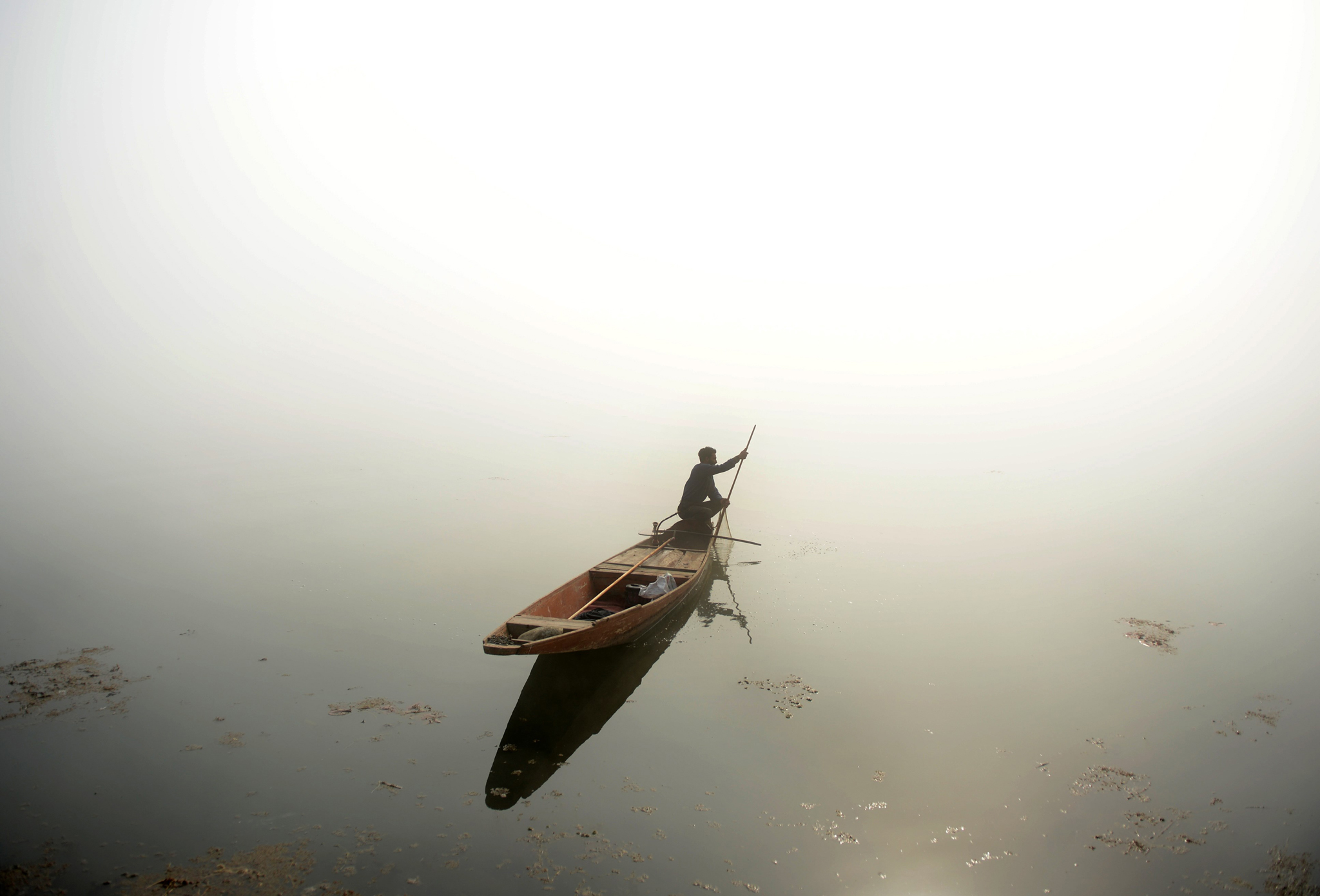 A Kashmiri fisherman rows his boat on Dal lake during dense fog in Srinaga