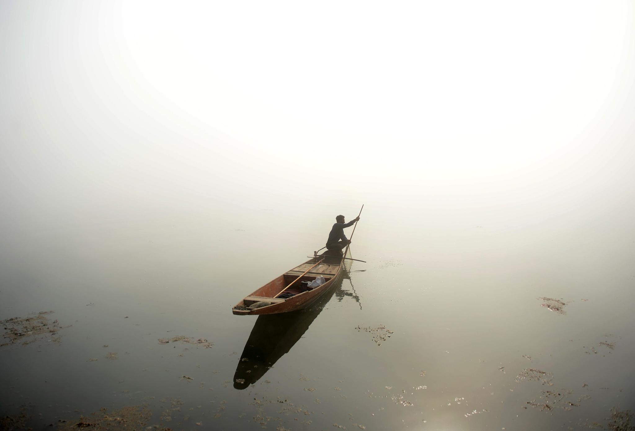 A Kashmiri fisherman rows his boat on Dal lake during dense fog in Srinaga