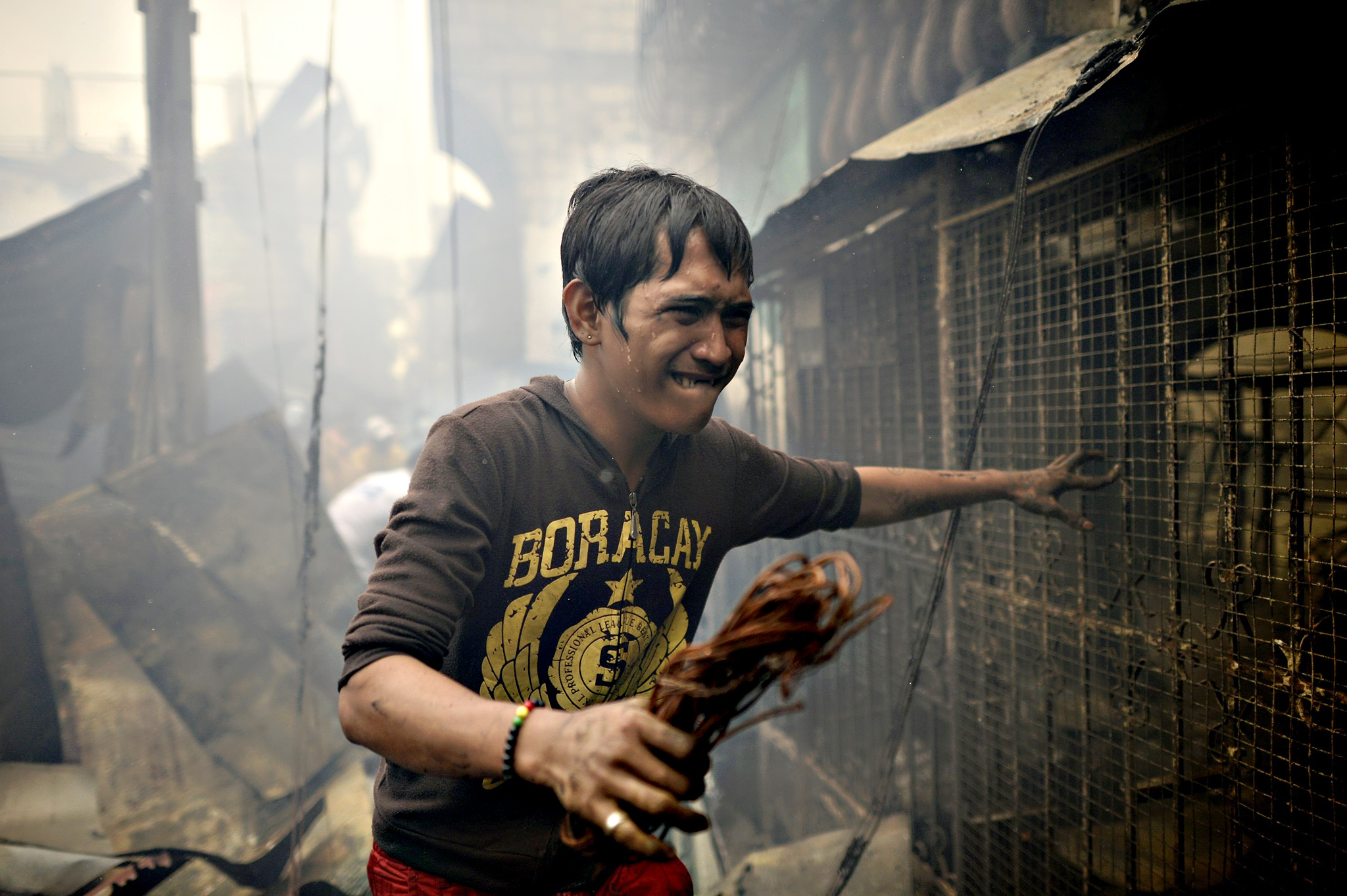 A resident walks amongst debris of destroyed houses after a fire razed a residential area in Manila on Friday. Almost 300 houses were destroyed on January 22, affecting more than 400 families according to the Bureau of Fire Protection (BFP)