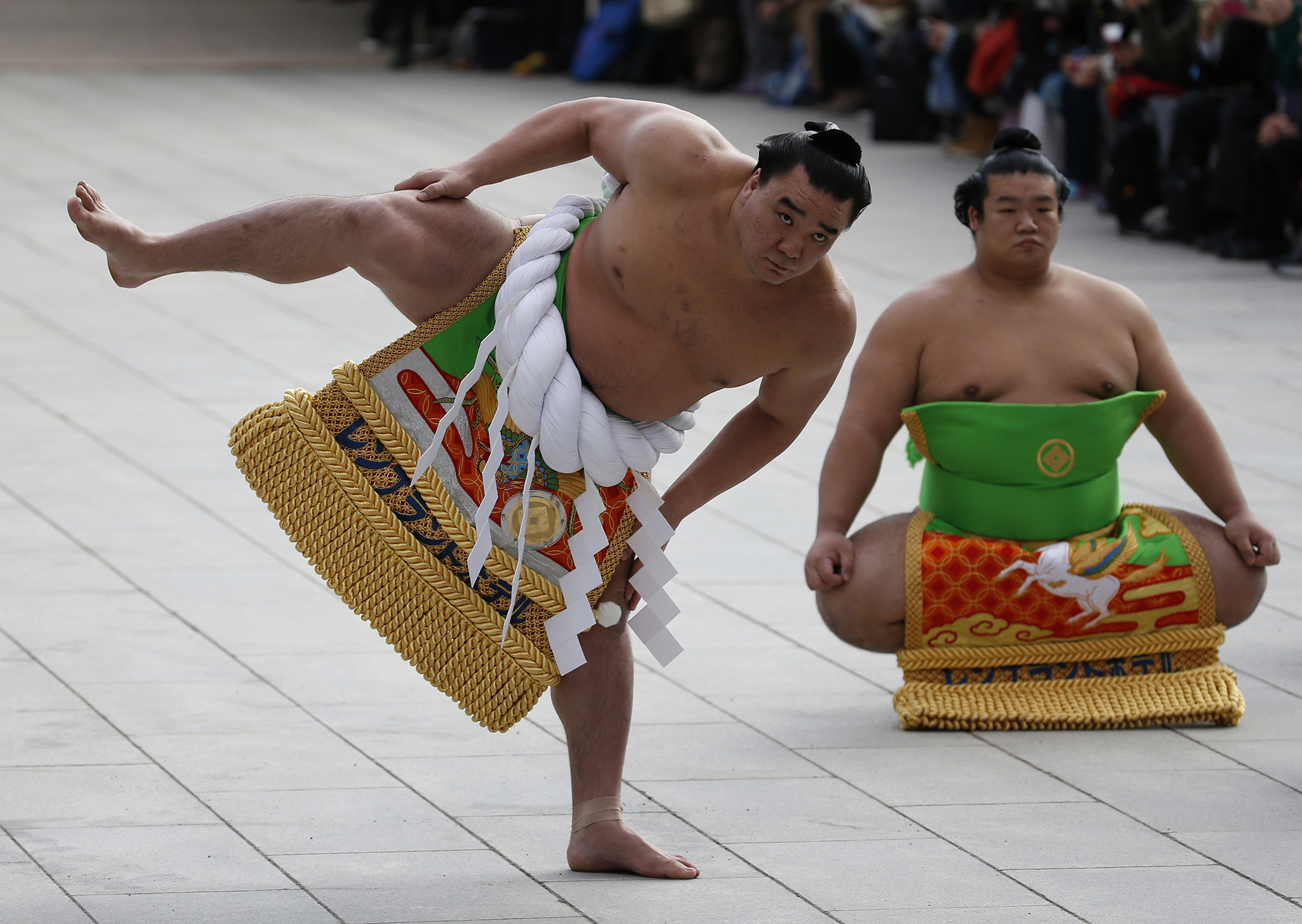 Mongolian-born grand sumo champion Yokozuna Harumafuji (L) performs the New Year's ring-entering rite at the annual celebration for the New Year at Meiji Shrine in Tokyo, Japan