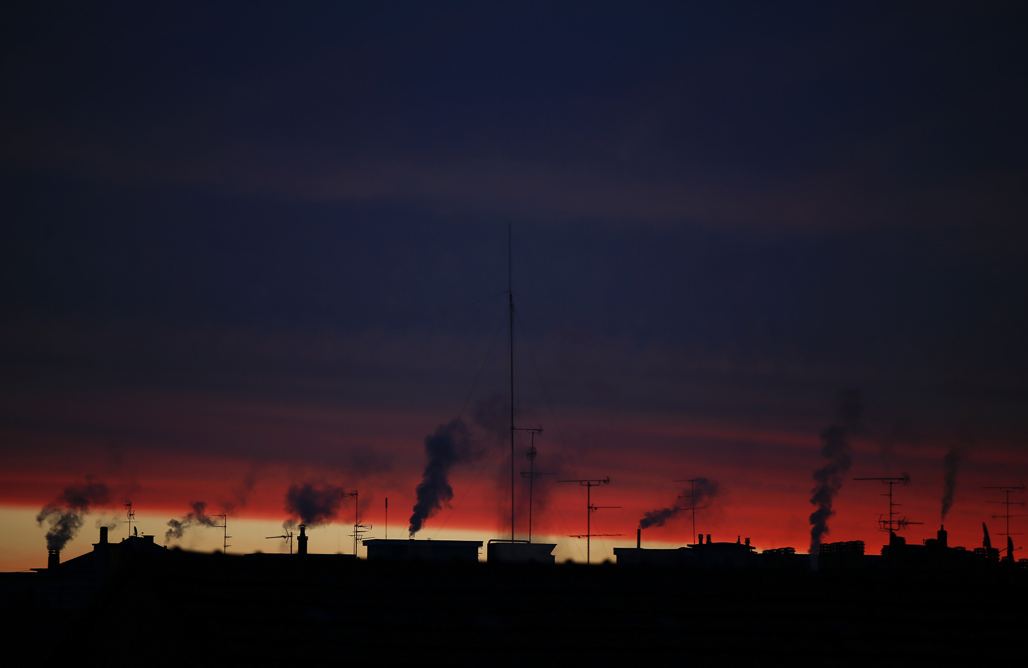 Smoke billows from chimneys of buildings as the sun rise in the early morning in Milan, Italy