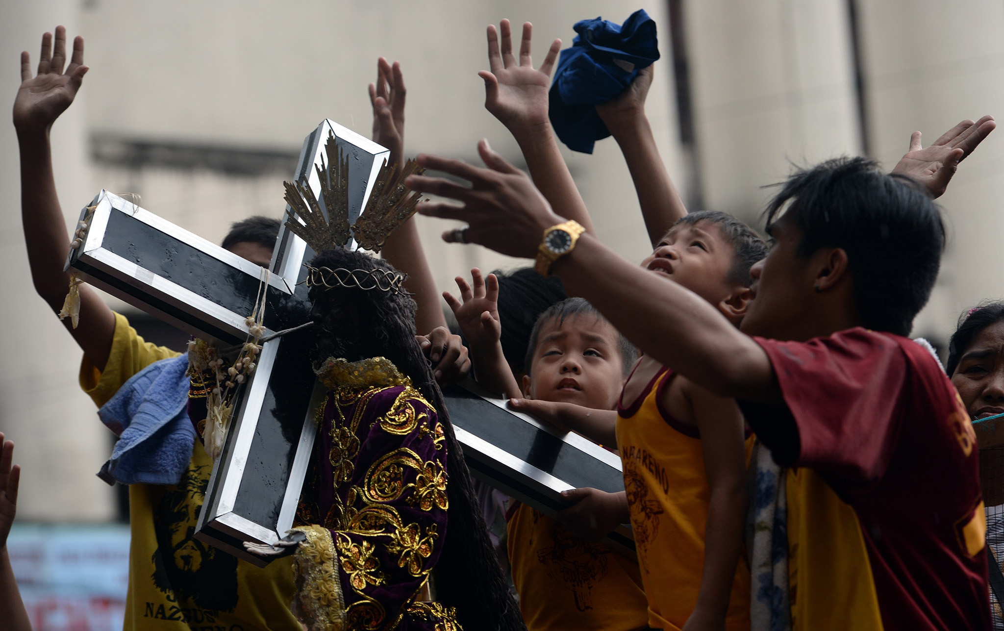 Devotees raise their hands next to a replica of the Black Nazarene in Manila ahead of the annual religious procession, during which hundreds of thousands of barefoot Catholic devotees will honour an ebony statue of Jesus Christ, which they believe has miraculous powers