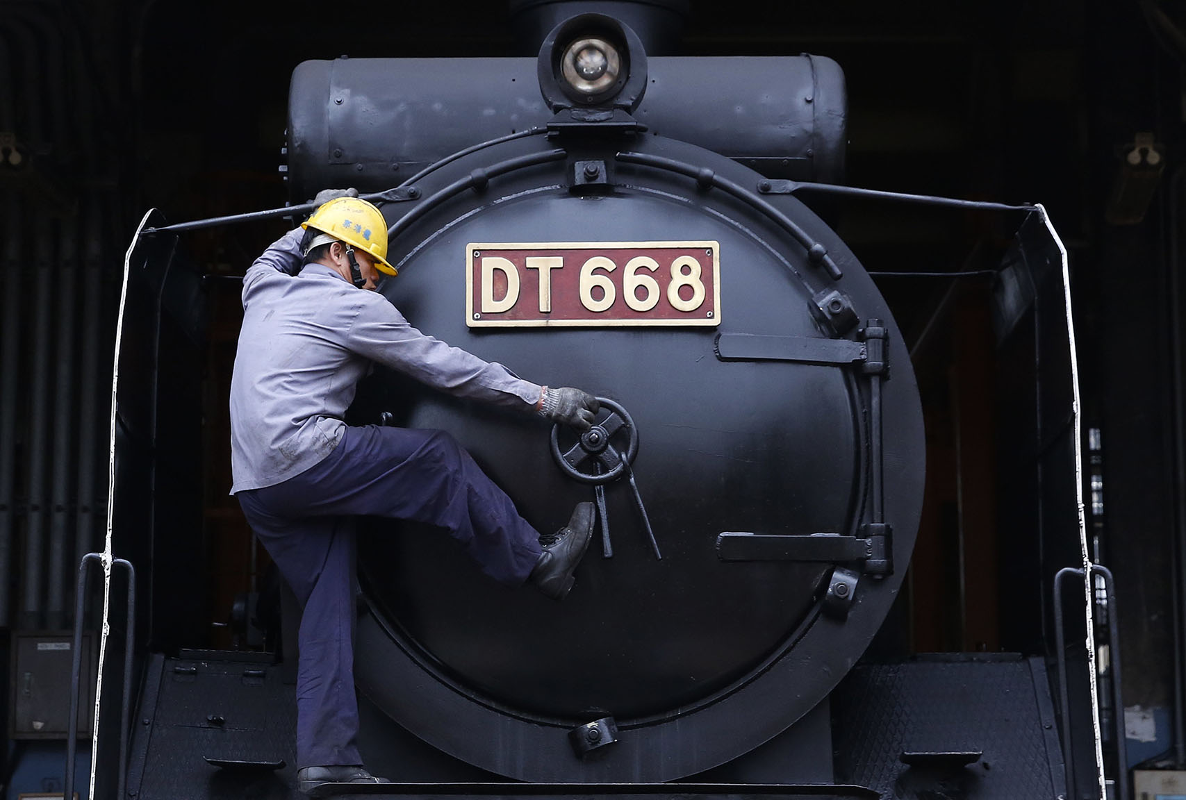 A workman opens the smokebox door of a Japanese-made steam train at a train depot in Changhua, Taiwan