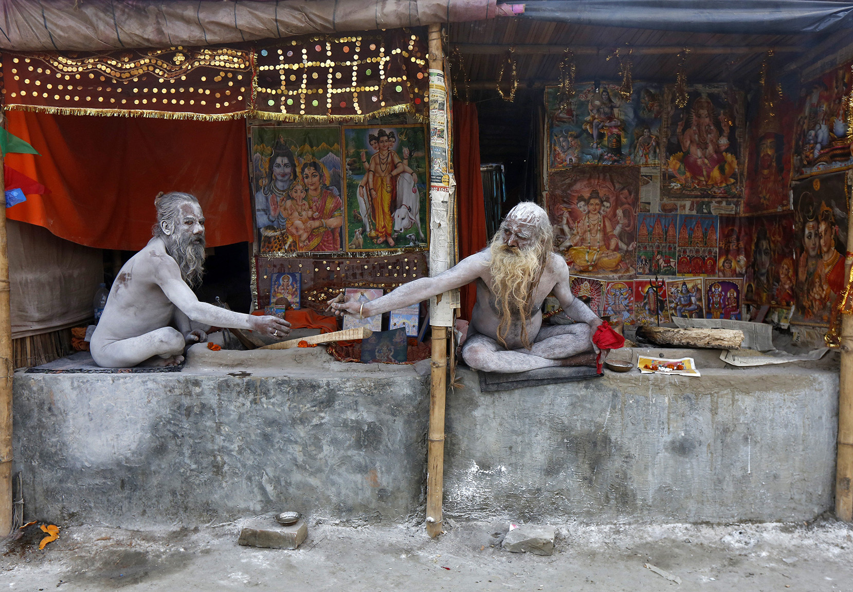 Naga Sadhus or Hindu holy men pass on a chillum to smoke inside their makeshift camps ahead of Makar Sankranti festival at Sagar Island
