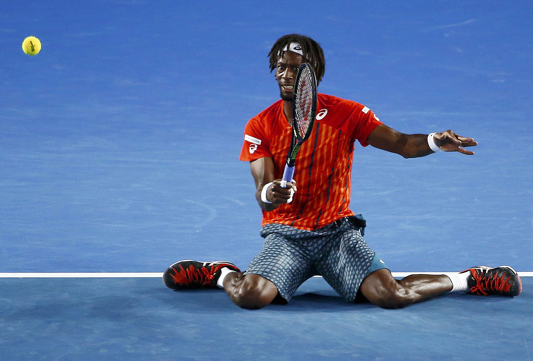 France's Monfils hits a shot on his knees during his quarter-final match against Canada's Raonic at the Australian Open tennis tournament at Melbourne Park