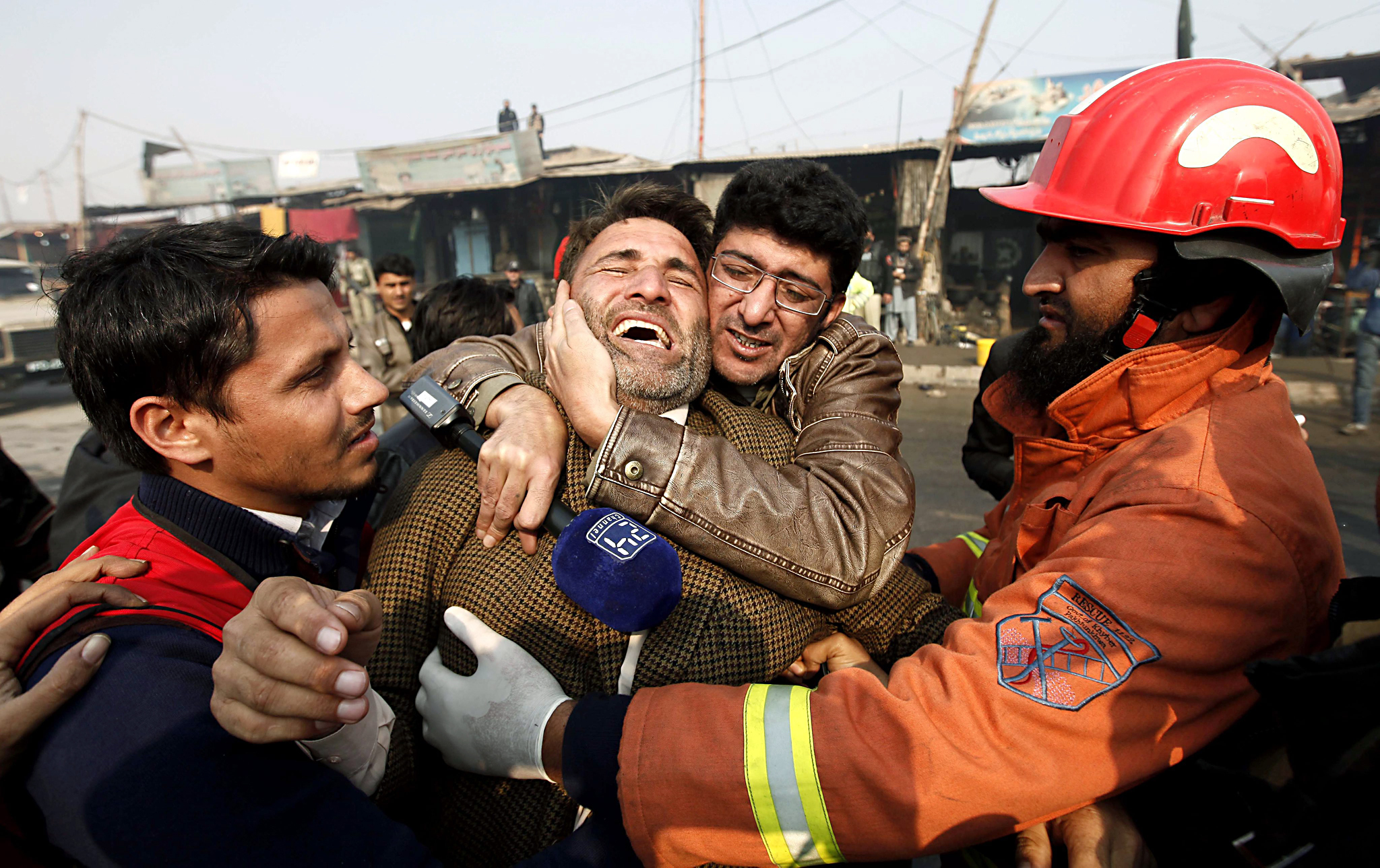 Bomb kills ten on Pakistan-Afghan highway...epa05110432 Rescue workers comfort a relative of victim of bomb blast, in Jamrud area of Khyber tribal district, Pakistan, 19 January 2016. A bomb hit a checkpoint in the north-western Pakistani city of Peshawar on 19 January, killing ten people and wounding over a dozen, officials said. Police guards and paramilitary troops guarding a highway leading to Afghanistan were targeted in Jamrud area of Khyber tribal district, officials said. The bomb was planted on a motorcycle parked near the checkpoint, Shah said, citing preliminary investigation findings.  EPA/ARSHAD ARBAB