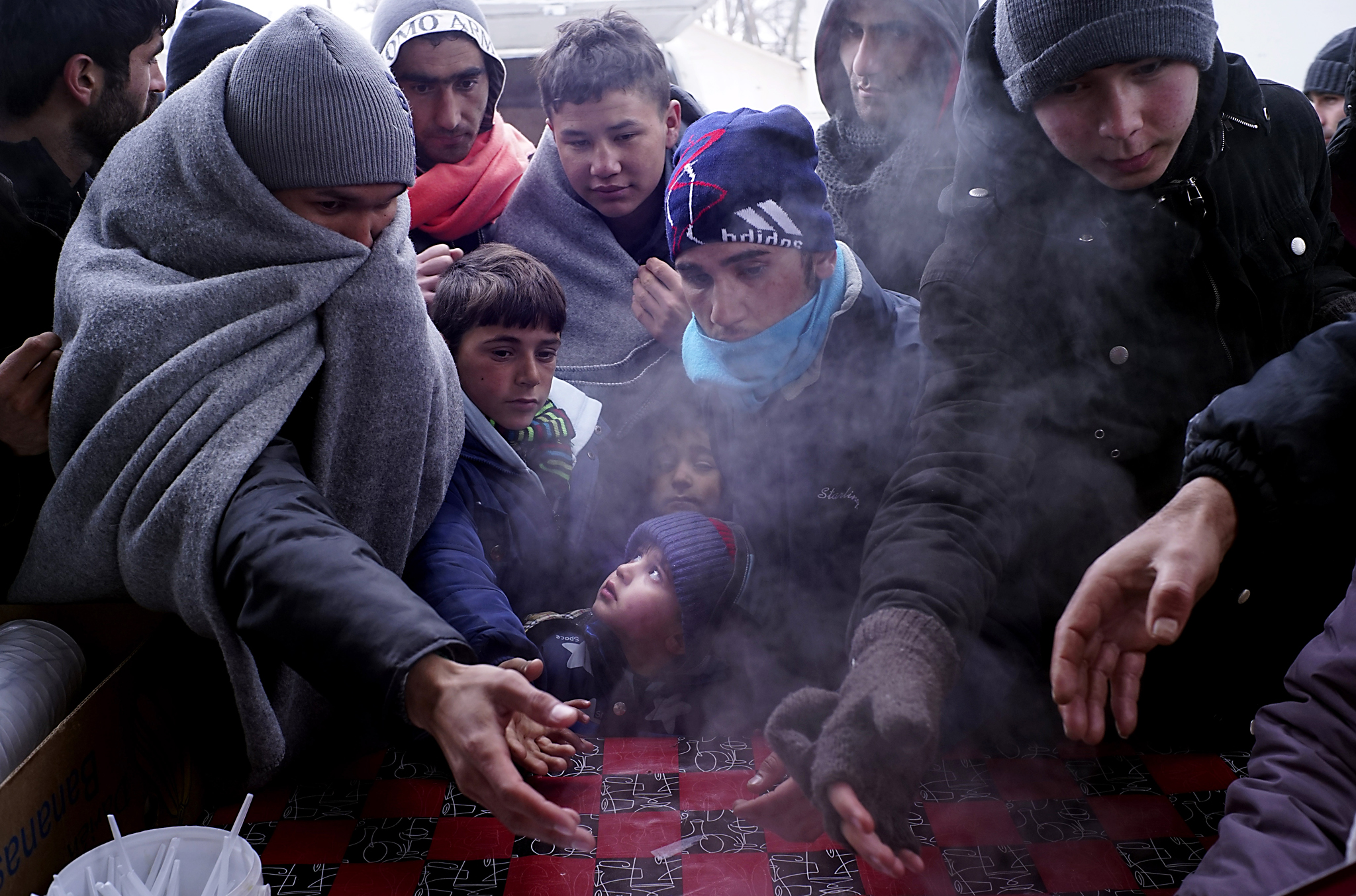 Migrants Wait For Trains In Sub Zero Temperatures On The Serbian Border...PRESEVO, SERBIA - JANUARY 26:  A group of migrant children wait for hot food in sub zero temperatures near the Serbian-Croatian border on January 26, 2016 in Presevo, Serbia.  Migrants have been braving sub zero temperatures as they cross the border from Macedonia into Serbia. (Photo by Milos Bicanski/Getty Images)