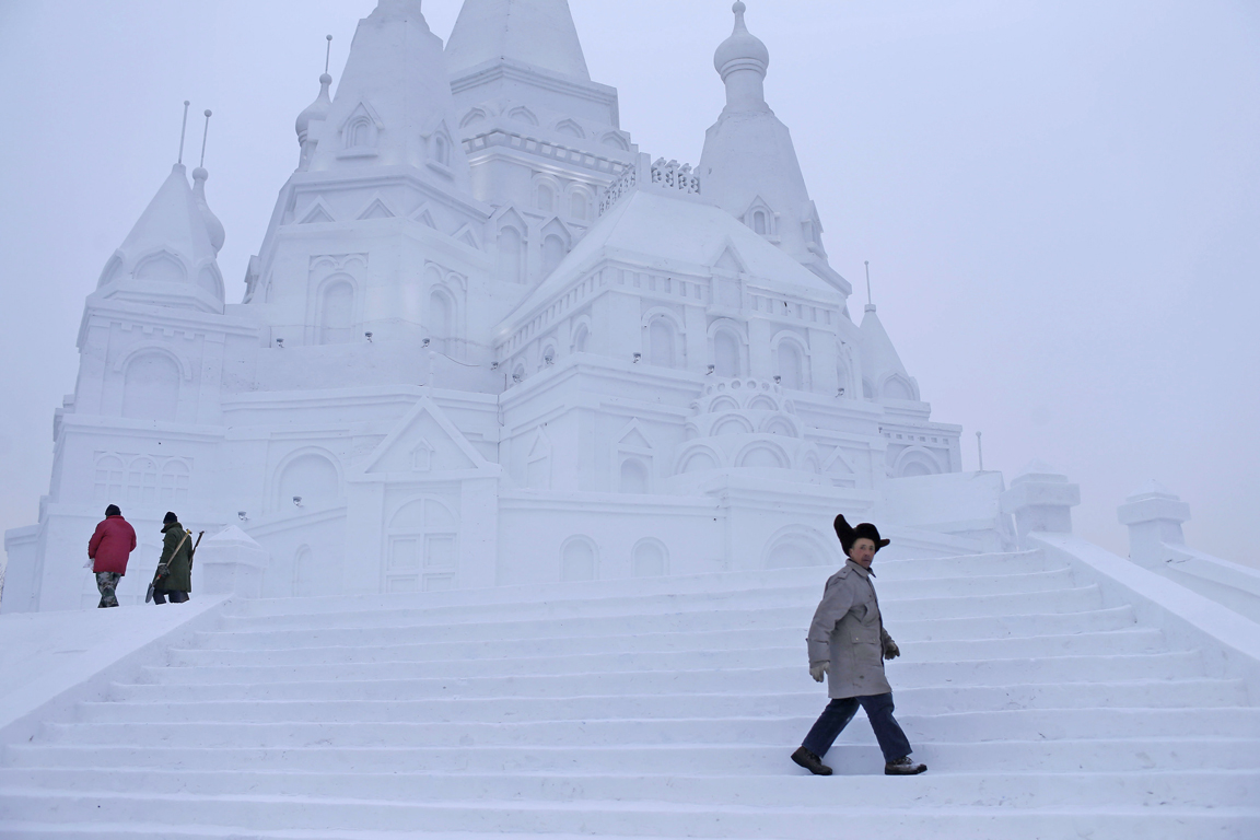 Laborers walk at a large snow sculpture ahead of the Harbin International Ice and Snow Festival in the northern city of Harbin, Heilongjiang province, China, January 5, 2016. REUTERS/Aly Song