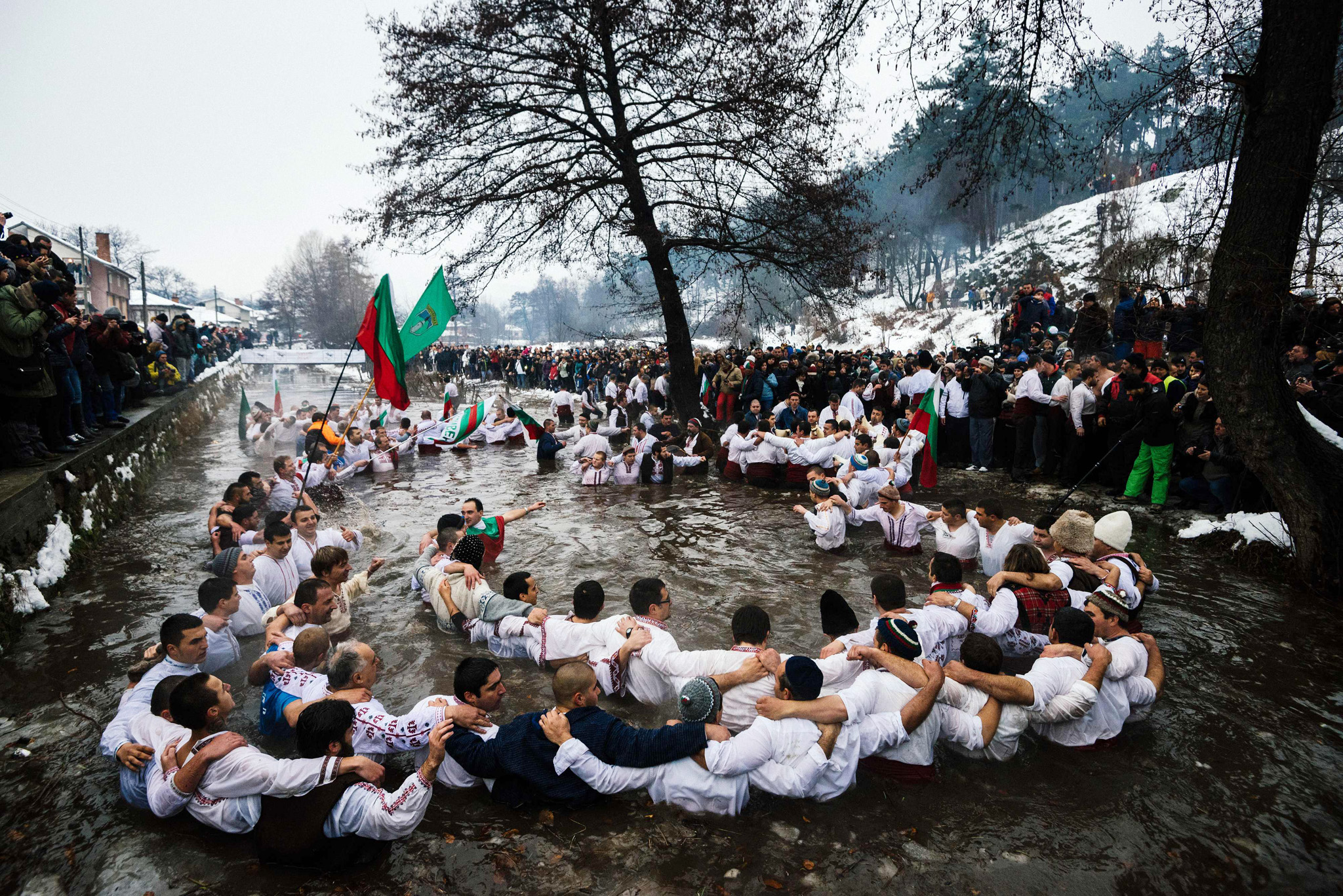 Men dance in the icy winter waters of th...Men dance in the icy winter waters of the Tundzha river in the town of Kalofer as part of the Epiphany Day celebrations on January 6, 2016.  As a tradition, an Eastern Orthodox priest throws a cross in the river and it is believed that the one who retrieves it will be healthy through the year as well as all those who dance in the icy waters.
