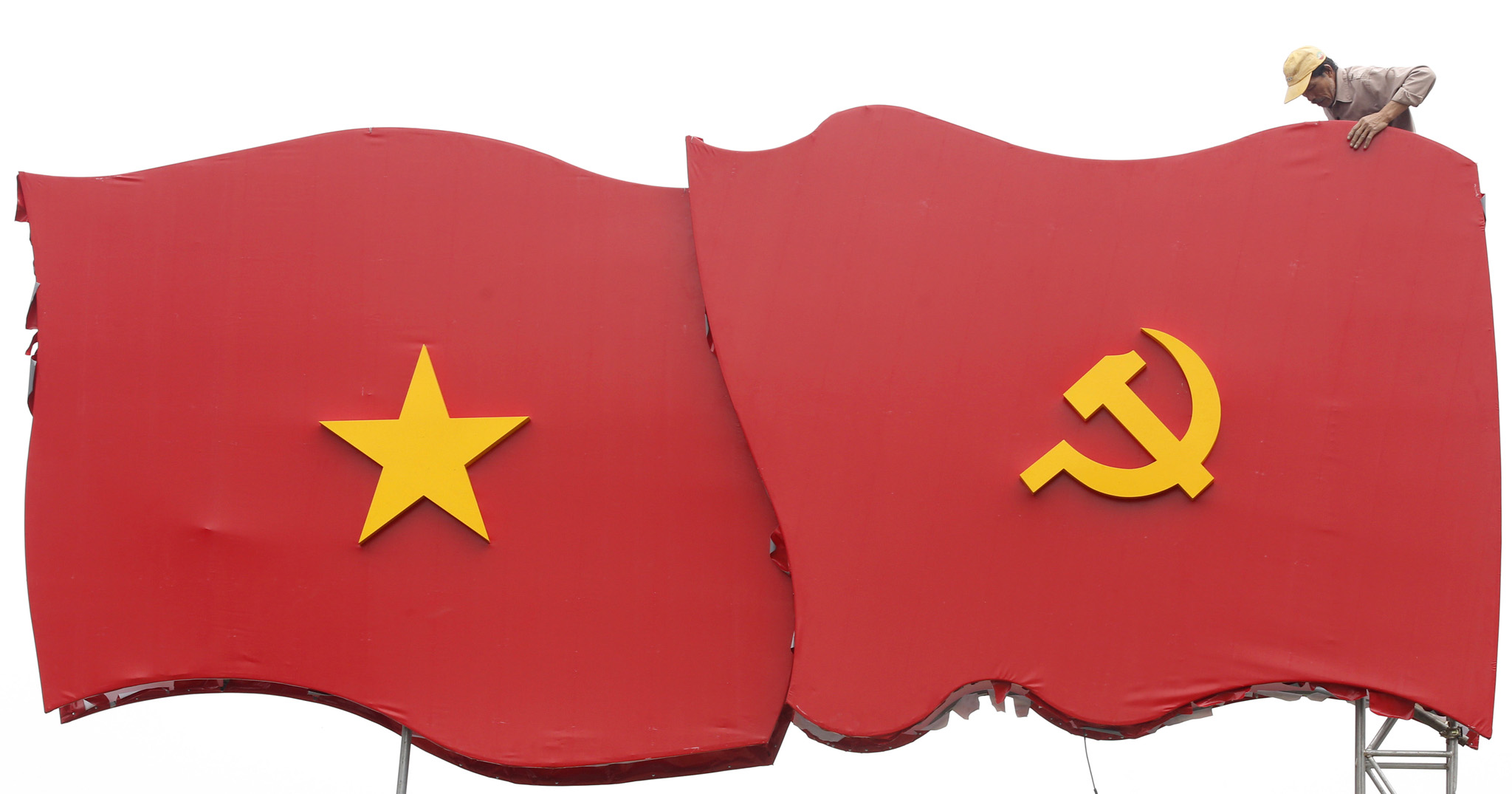 A worker erects decoration with images of the Vietnamese national flag and communist flag before the upcoming 12th national congress of the ruling Communist Party of Vietnam on a street in Hanoi...A worker erects decoration with images of the Vietnamese national flag (L) and communist flag before the upcoming 12th national congress of the ruling Communist Party of Vietnam (CPV) on a street in Hanoi January 4, 2016.