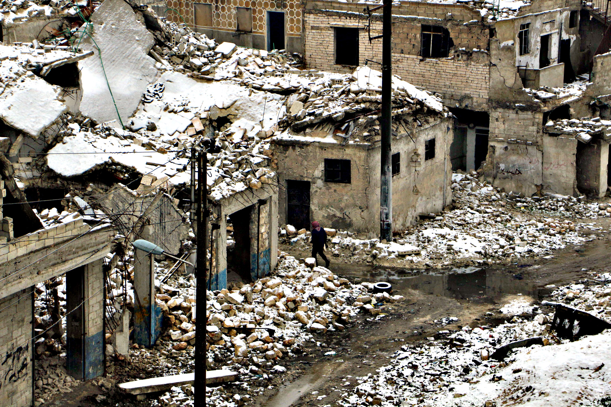 A Syrian man walks past damaged homes following a snow storm in the northern Syrian city of Aleppo on Tuesday. The conflict in Syria has killed more than 250,000 people and forced millions to flee their homes since it broke out in March 2011.