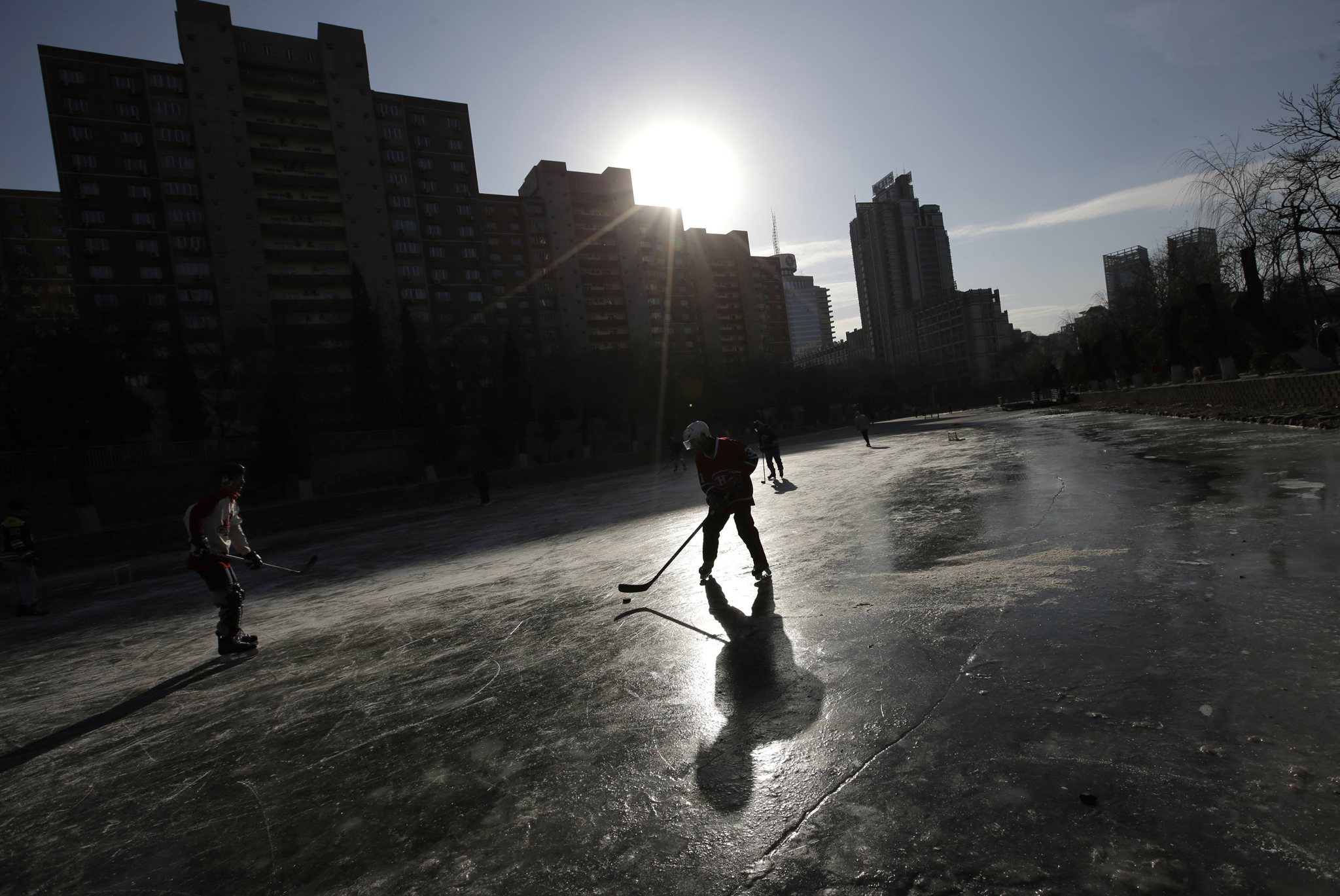 People play ice hockey on the frozen Liangmahe River in Beijing