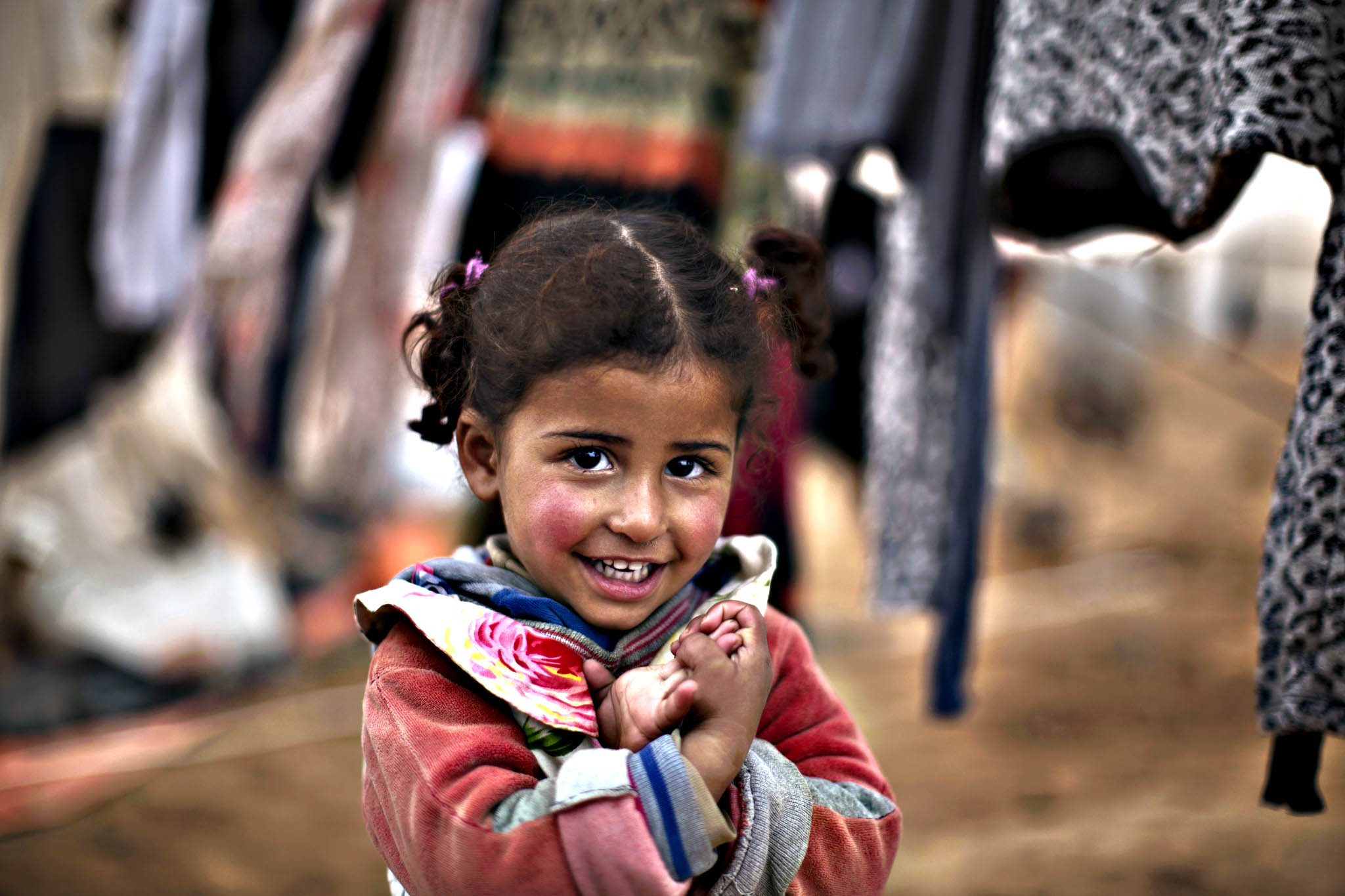 Syrian refugee Bissan Alabdullah, almost 3, smiles while standing next to her family's laundry outside their tent at an informal tented settlement near the Syrian border on the outskirts of Mafraq, Jordan, Wednesday, Jan. 20, 2016.