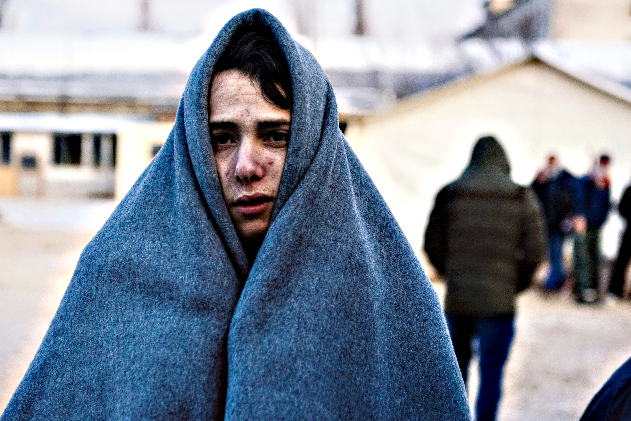 A migrant wrapped in a blanket to keep warm waits at a registration camp in southern Serbian town of Presevo on January 22, 2016, after crossing the Macedonian border.  As refugees continued to flow from Greece through the Balkans on their way to western Europe, aid workers sounded alarms over inadequate shelter from the current freezing temperatures and snowy conditions, particularly for children.
