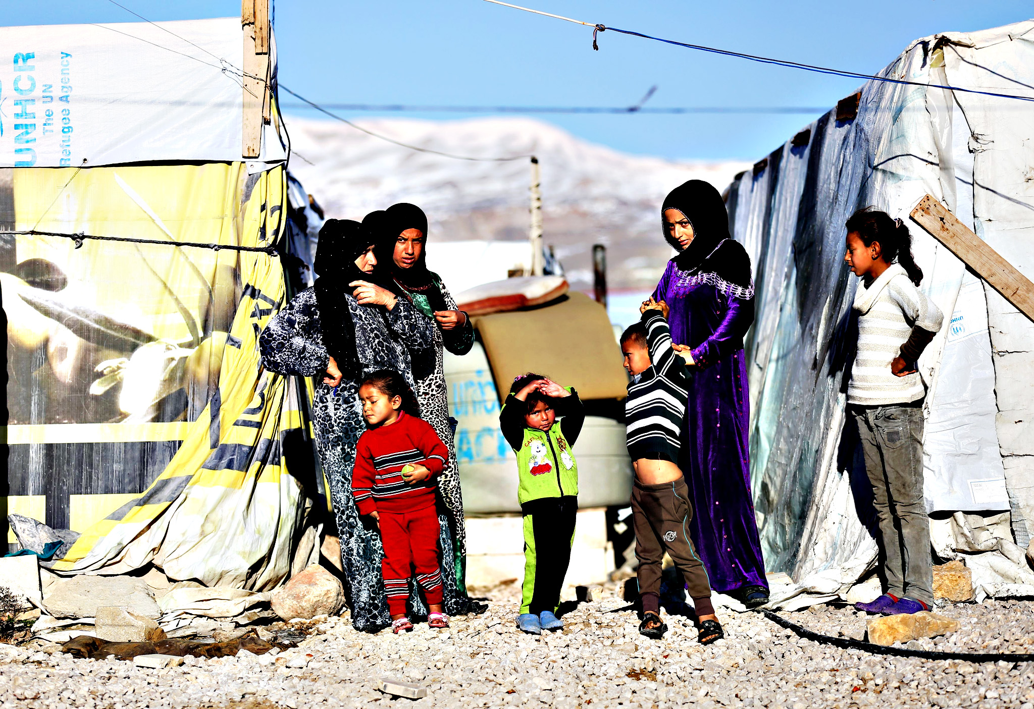 Syrian refugees look on during a visit by Secretary of State for International Development Justine Greening, during her visit to an Informal Tented Settlement occupied by Syrian refuges close to the Syrian boarder in Lebanon, to see how the UK's response and aid is helping the refugee crisis. PRESS ASSOCIATION Photo. Picture date: Friday January 15, 2016.