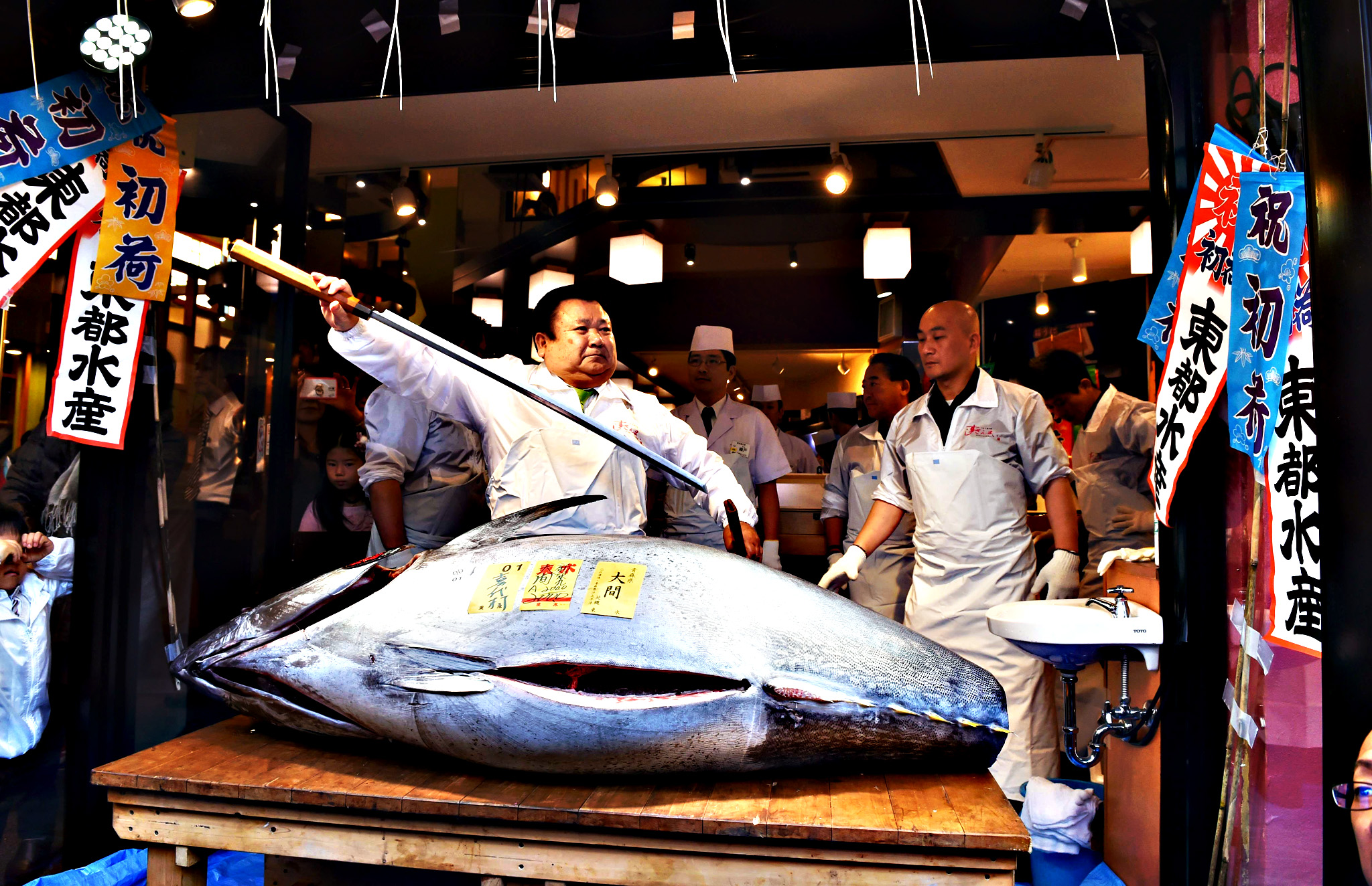 President of sushi restaurant chain Sushi-Zanmai, Kiyoshi Kimura (C) holds a long fish knife as he poses with a 200-kilogram bluefin tuna at his main restaurant near Tokyo's Tsukiji fish market on January 5, 2016. The bluefin tuna was traded at 117,000 USD (14 million yen) at the wholesale market on the first trading day of the new year. Tsukiji market will close its doors after 80 years followed by a new market opening in Toyosu this autumn.