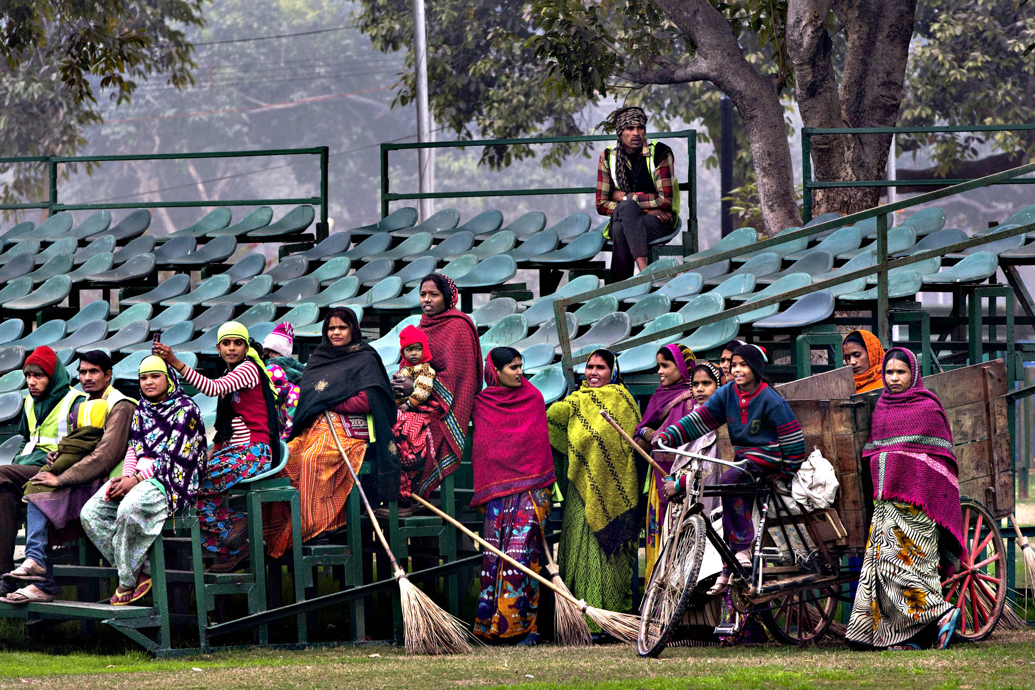 Indian sweepers and laborers take time out to watch different branches of Indian military practice a march past as they rehearse to participate in the Republic Day parade in New Delhi, India, Wednesday, Jan. 20, 2016. India celebrates Republic Day on Jan. 26 every year, highlighted by a march past by different branches of the military as well as a display of arms and missiles.