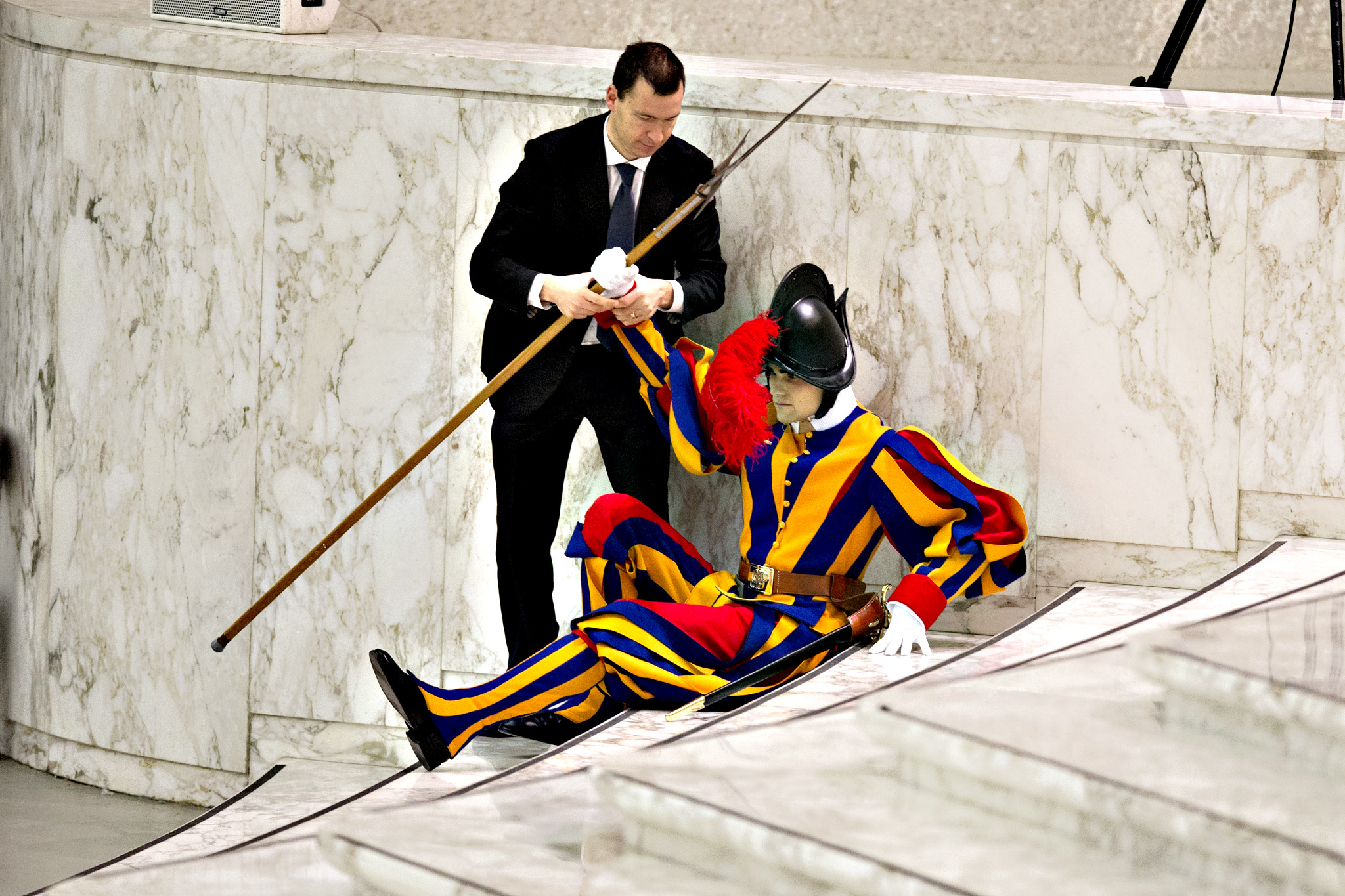 A Swiss Guard is assisted after falling during Pope Francis' weekly general audience in the Paul VI Hall at the Vatican, Wednesday, Jan. 13, 2016.
