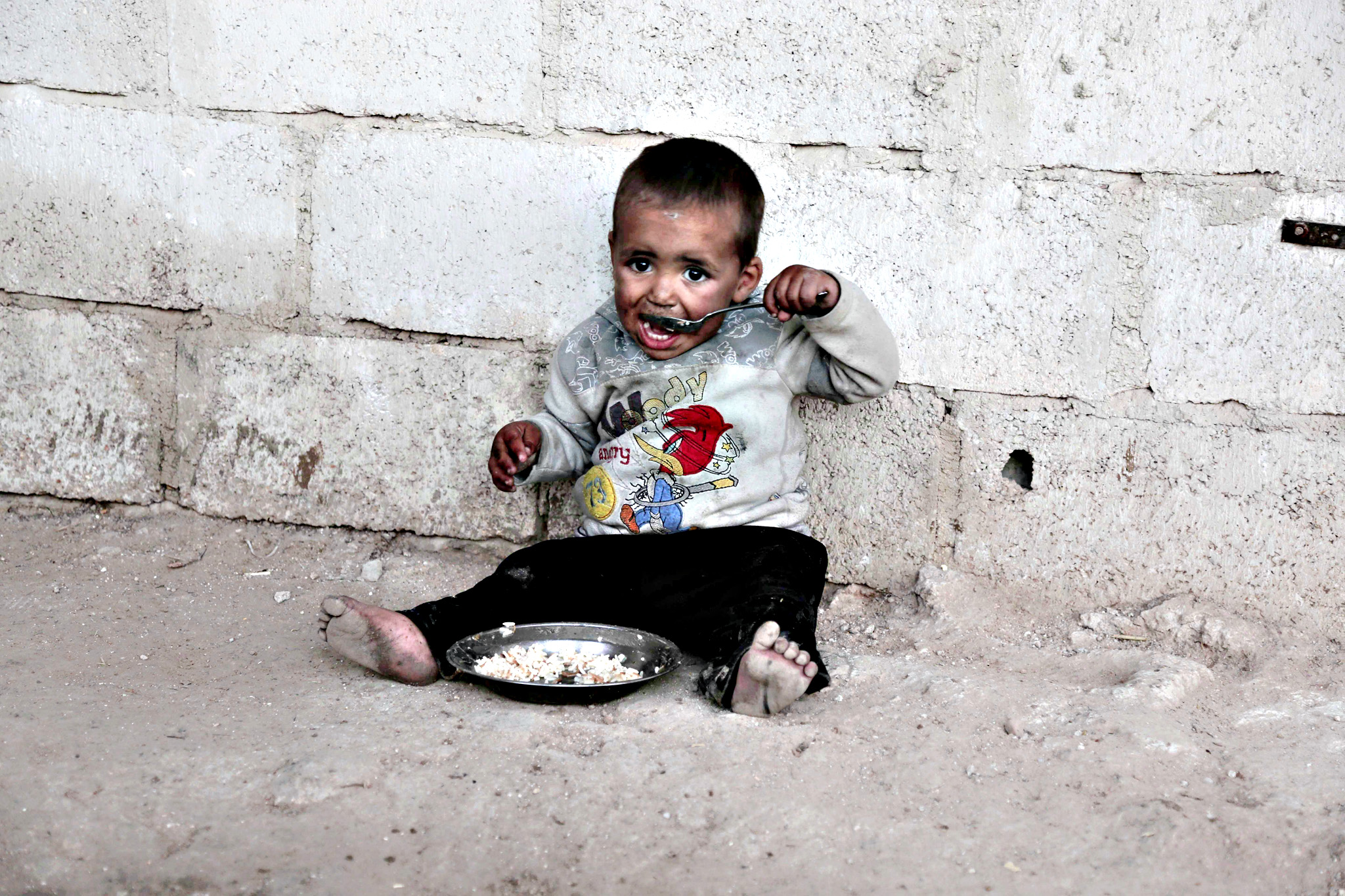 ..A child from the Abu Sleiman family has a lunch at his house in the Syrian town of Beit Nayem, in the rebel-held Eastern Ghouta region on the outskirts of the capital Damascus. Abu Sleiman, 39, has eleven children and two wives. He got injured in 2014 in a Syrian government air strike on his house in the nearby village of Marj al-Sultan and cannot work anymore.