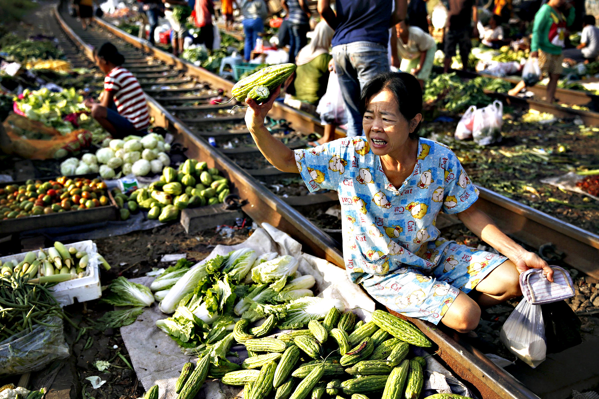 A customer asks for the price of a bittergourd at Duri market on a railway track in Jakarta, on Friday. Indonesia's annual inflation rate cooled to the lowest in six years in December, which might pave the way for the central bank to cut a benchmark rate held at 7.50 percent since February 2015.