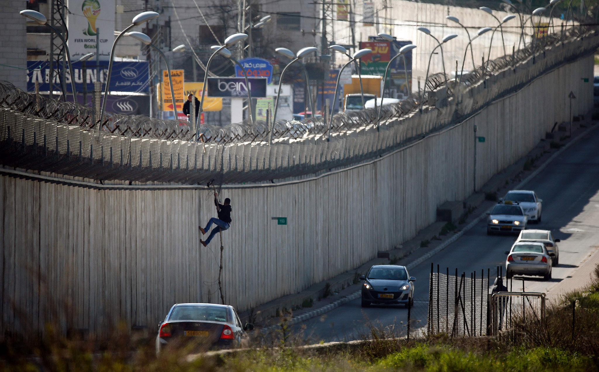 A Palestinian man uses a rope to climb over a section of Israel's controversial separation barrier that separates the West Bank city of al-Ram from east Jerusalem