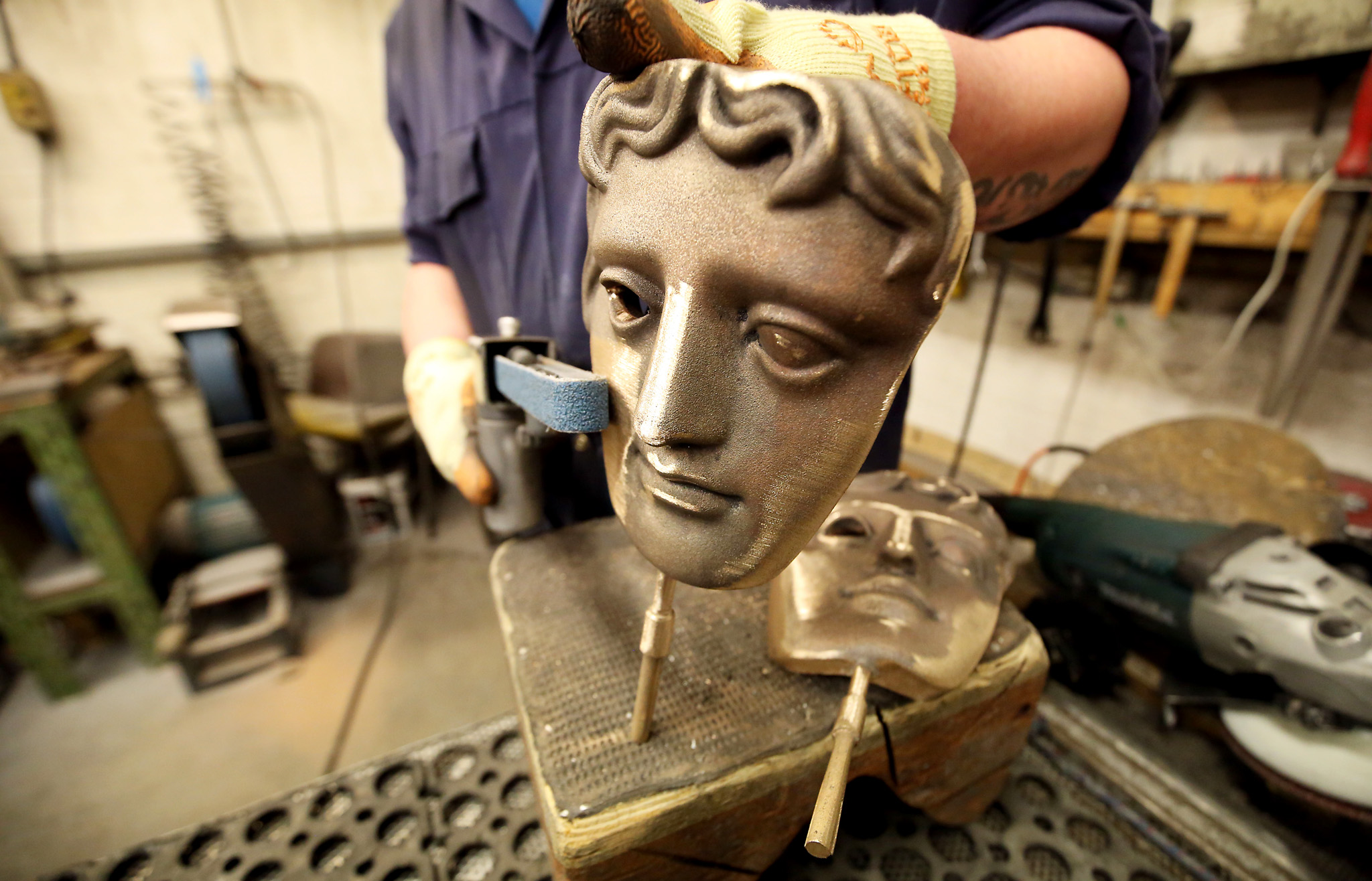 BAFTA preparations...Fettler Piotr Lichon sands a bronze statue to  create a BAFTA mask at New Pro Foundries in West Drayton, Middlesex, ahead the ceremony later this month. PRESS ASSOCIATION Photo. Picture date: Thursday February 4, 2016. Designed by US sculptor Mitzi Cunliffe in 1955, New Pro Foundries has been making the bronze casts since the ceremony was created in 1976. Photo credit should read: Steve Parsons/PA Wire