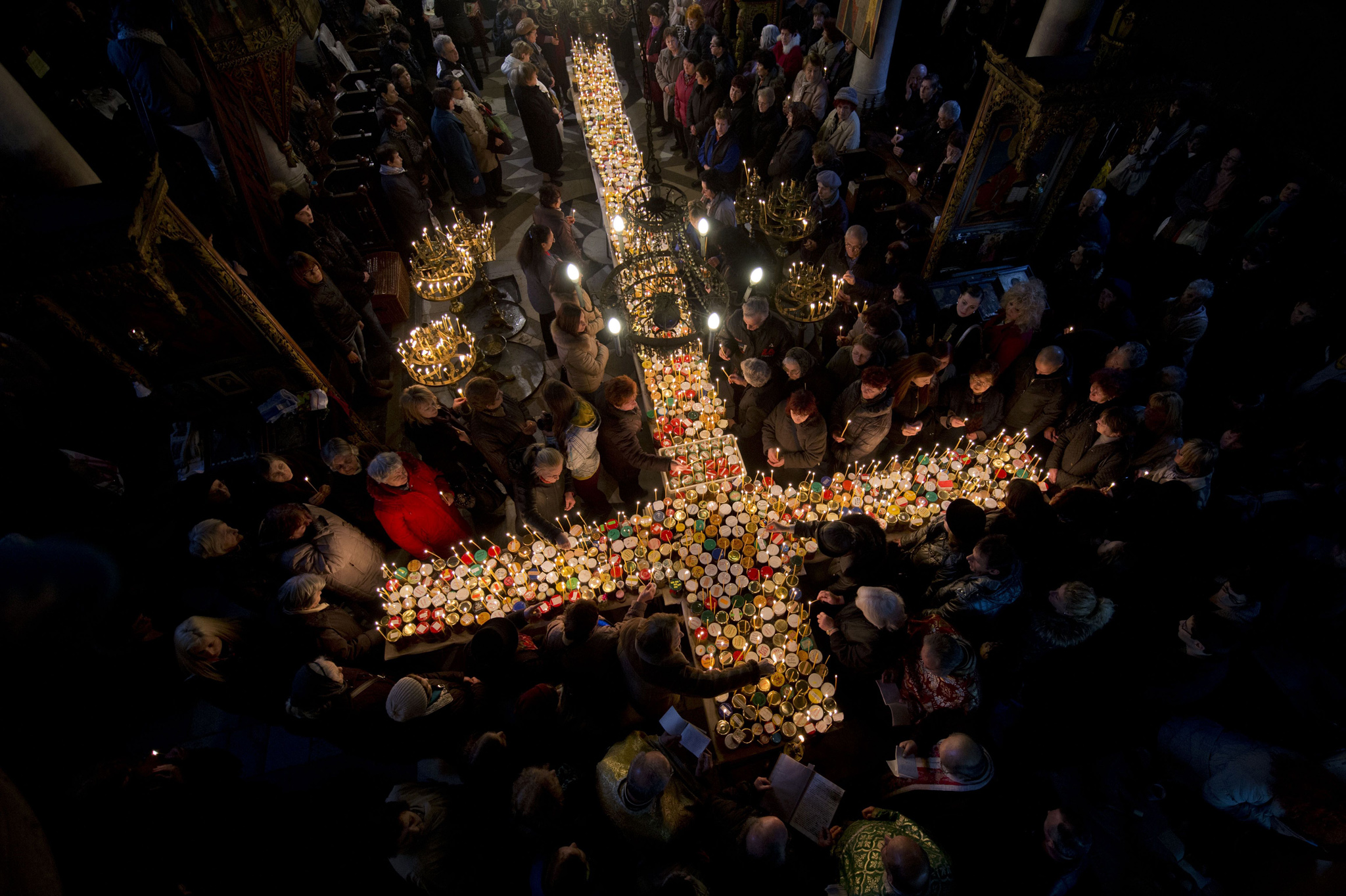 Believers pray around a cross-shaped platform covered with candles placed in jars of honey during a ceremony marking the day of Saint Haralam
