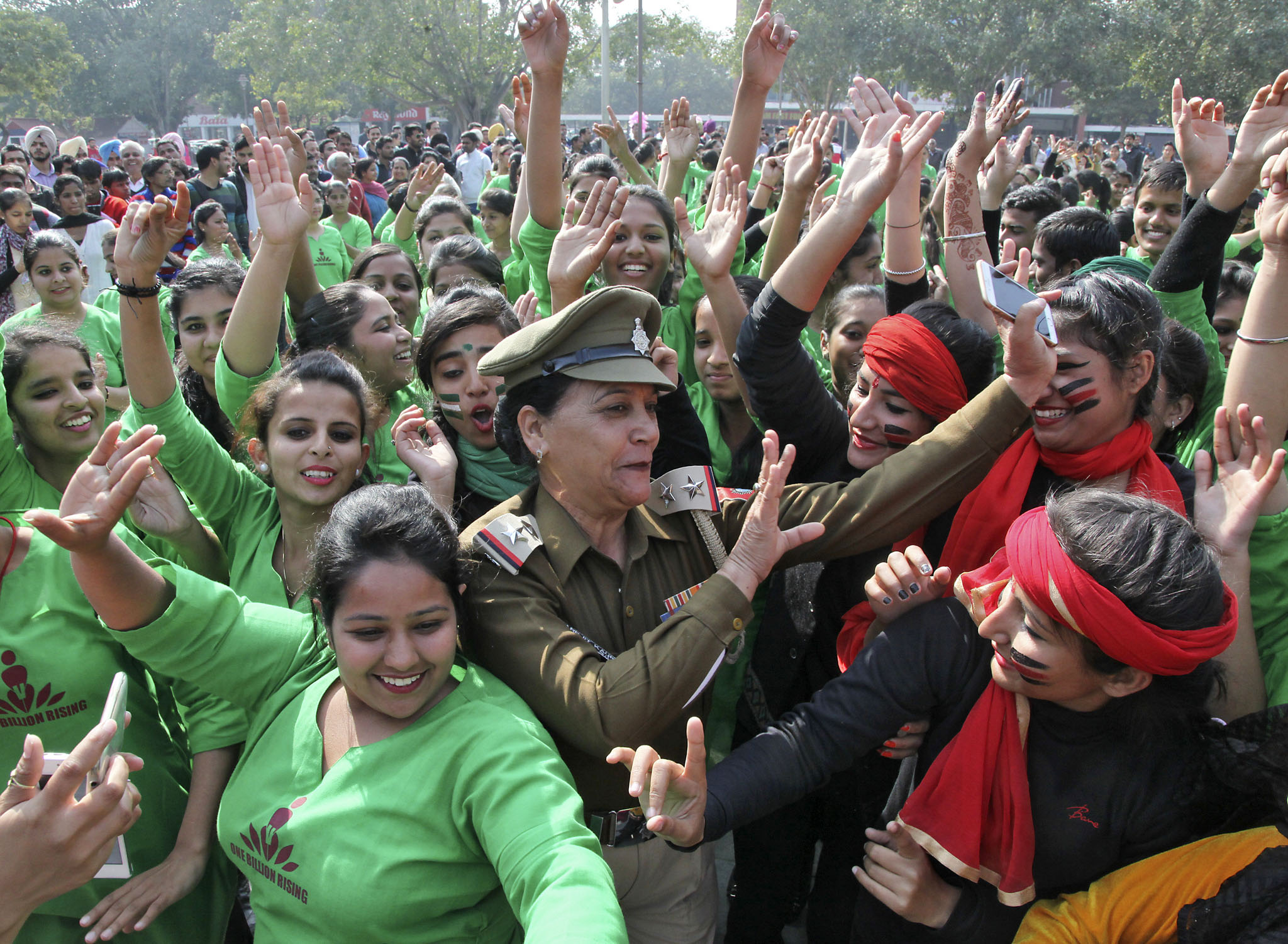 "Students and a women police officer dance as they take part in ""One Billion Rising"" campaign on a street in Chandigarh...Students and a women police officer (C) dance as they take part in ""One Billion Rising"" campaign on a street in Chandigarh, India, February 2, 2016. One Billion Rising is a global coordinated campaign aimed to call for an end to violence against women and girls, according to its organisers. REUTERS/Ajay Verma"