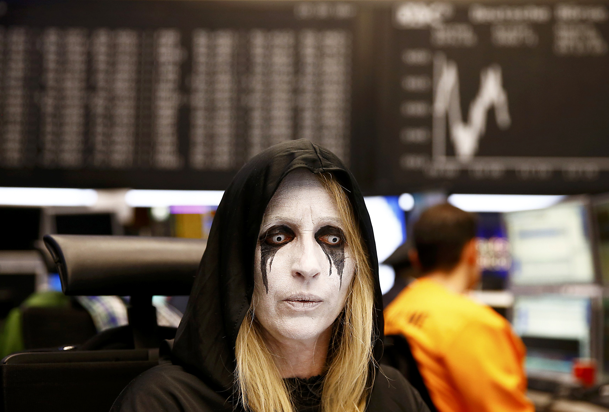 Share traders dressed in carnival costumes work a their desks in front of the DAX index at the stock exchange on Shrove Tuesday in Frankfurt...Share traders dressed in carnival costumes work a their desks in front of the DAX index at the stock exchange on Shrove Tuesday in Frankfurt, Germany February 9, 2016. Frankfurt's bourse traders follow a long tradition by wearing carnival costumes on Shrove Tuesday.  REUTERS/Kai Pfaffenbach