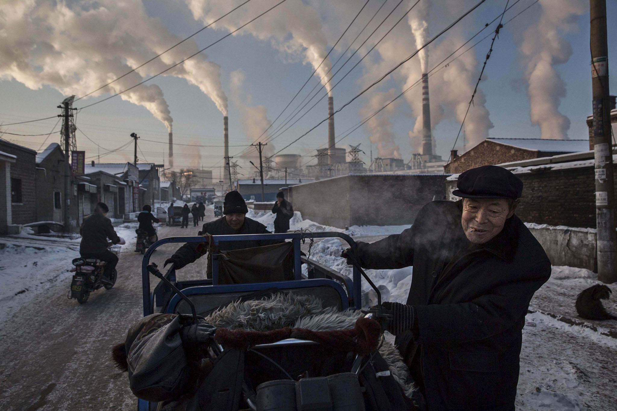 Daily Life, 1st prize singles, World Press Photo Awards (Kevin Frayer - China's Coal Addiction)Chinese men pull a tricycle in a neighborhood next to a coal-fired power plant in Shanxi, China, November 26, 2015