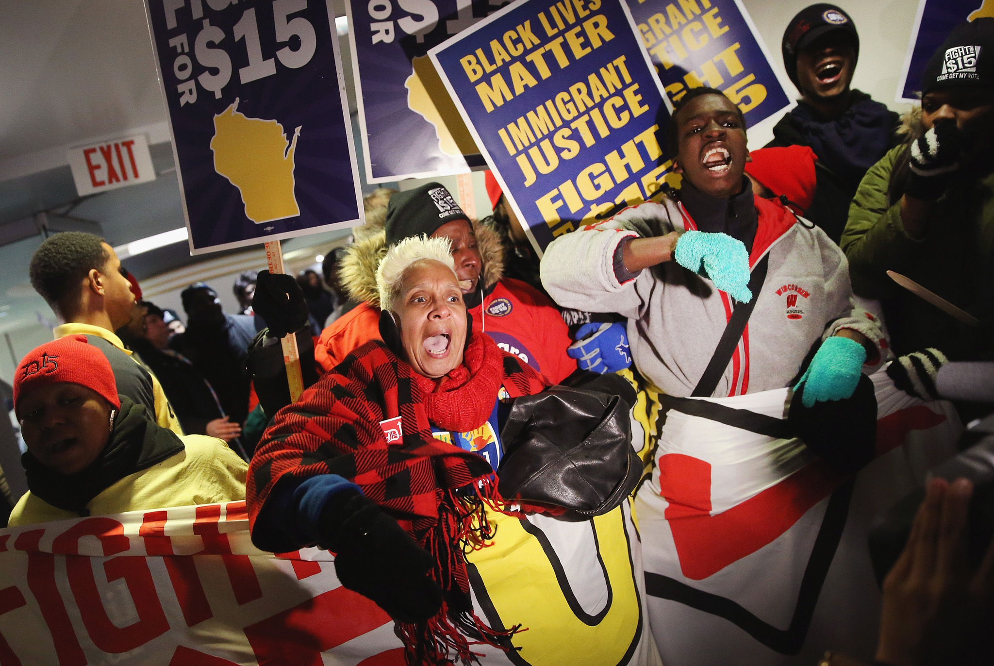 Demonstrators protesting for an increase in the minimum wage enter the media file center at the PBS NewsHour Democratic presidential candidate debate at the University of Wisconsin-Milwaukee