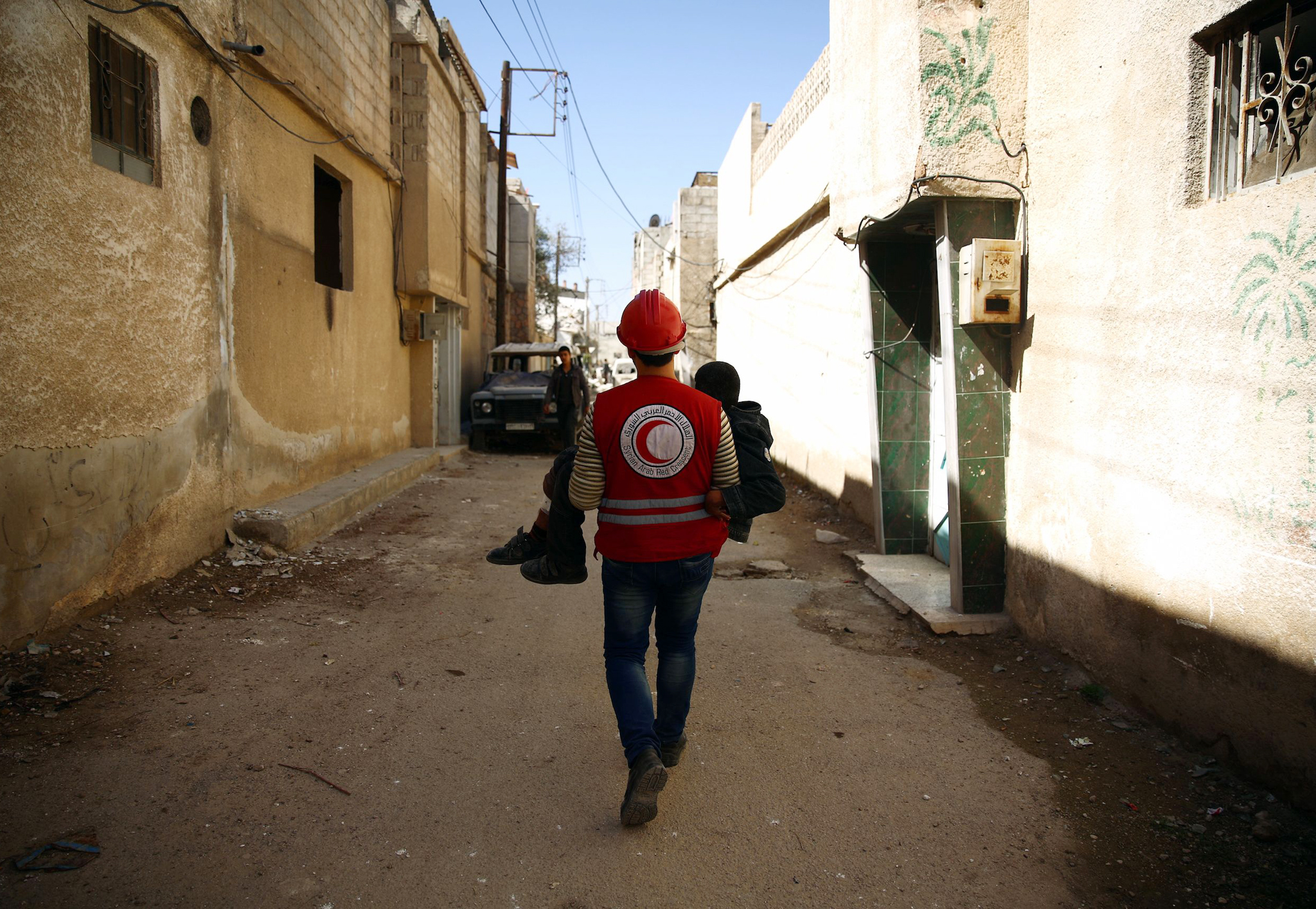 A member of the Syrian Arab Red Crescent...A member of the Syrian Arab Red Crescent carries a wounded boy following an airstrike in the rebel-held city of Douma in Eastern Ghouta, on February 26, 2016. Intense Russian air strikes and regime shelling battered rebel bastions across Syria, the Syrian Observatory for Human Rights said, just hours before a midnight deadline for a landmark ceasefire in the country's five-year civil war. / AFP / Abd DoumanyABD DOUMANY/AFP/Getty Images