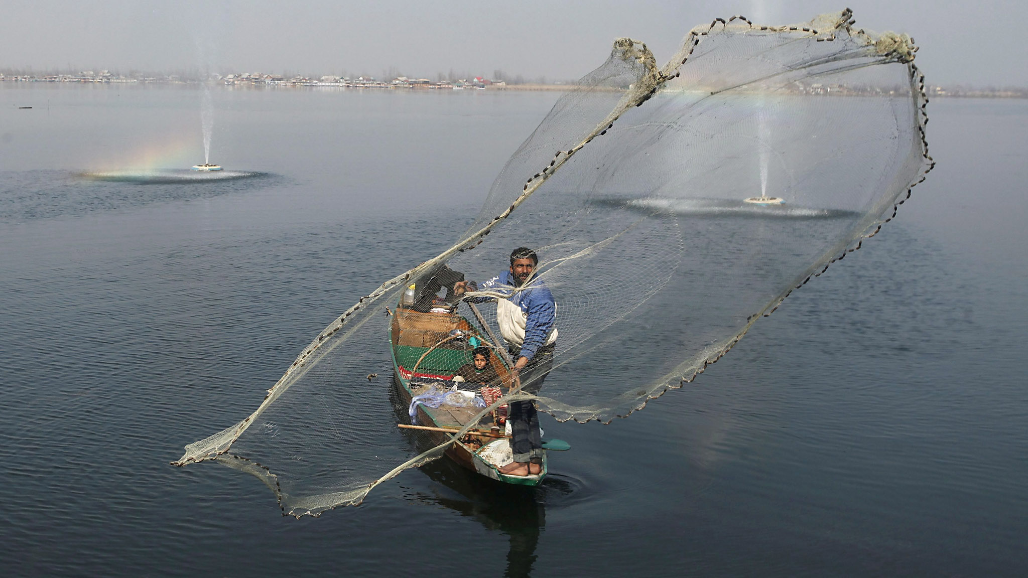 Daily Life in Srinagar ...epa05167710 A Kashmiri fisherman on Dal Lake in Srinagar, the summer capital of Indian Kashmir, 18 February 2016. The temperature in the Kashmir valley has risen and people are out enjoying the warmer weather.  EPA/FAROOQ KHAN